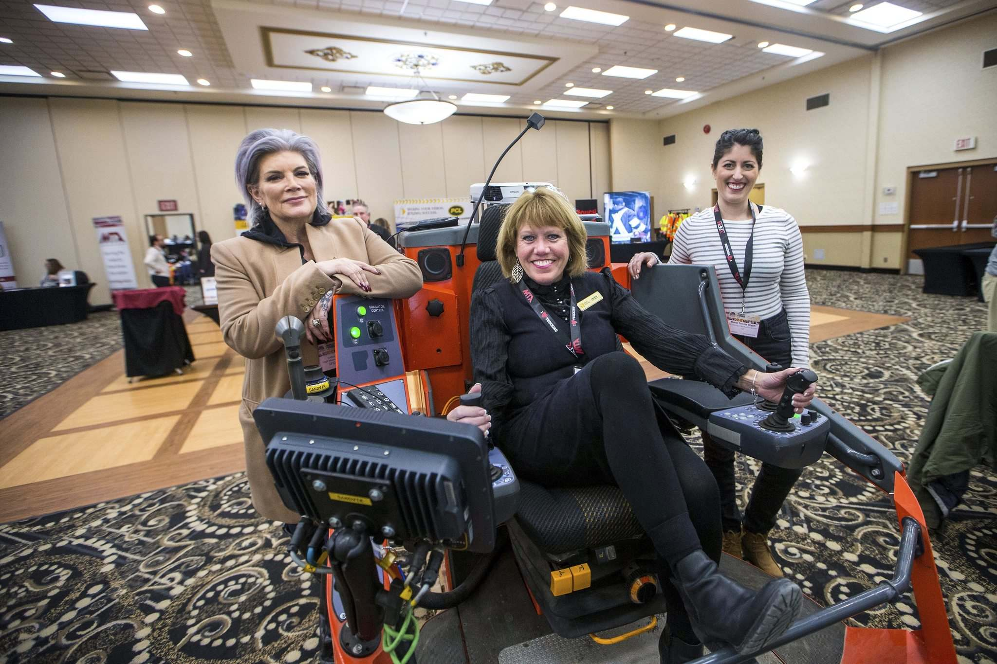 MIKAELA MACKENZIE / WINNIPEG FREE PRESS</p><p>Muriel Torchia Shyjak, owner of MG Electrical/Mechanical Services (left), Carol Paul, head of the construction sector council, and Colleen Munro, head of Munro Construction with a blast hole drilling simulator at the Women in Trades conference at Victoria Inn Hotel & Convention Centre in Winnipeg on Tuesday.</p>