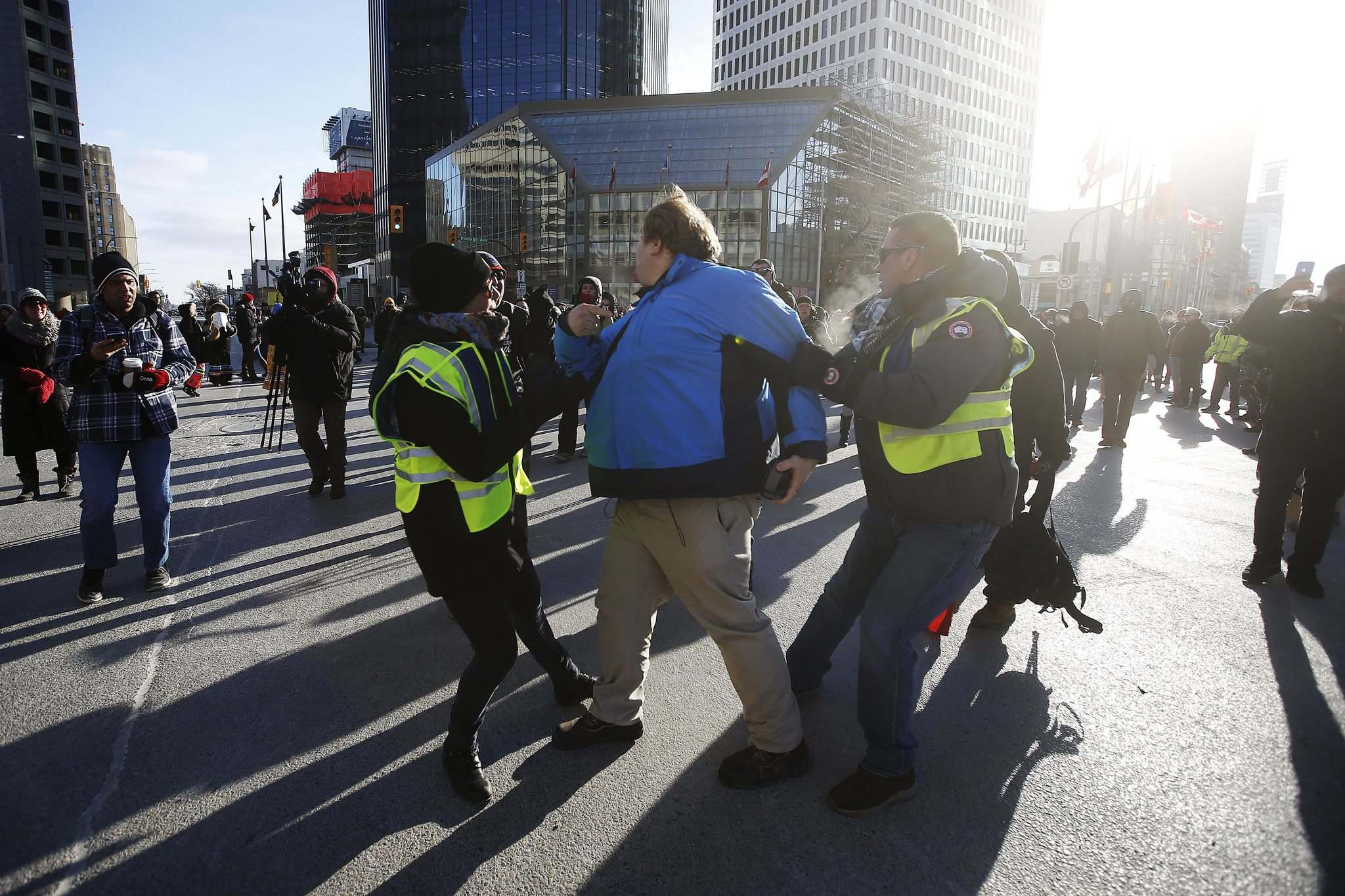 JOHN WOODS / WINNIPEG FREE PRESS FILES</p><p>A man who confronted protesters as they blocked Portage and Main on Feb. 26 is taken away from the demonstration.</p>