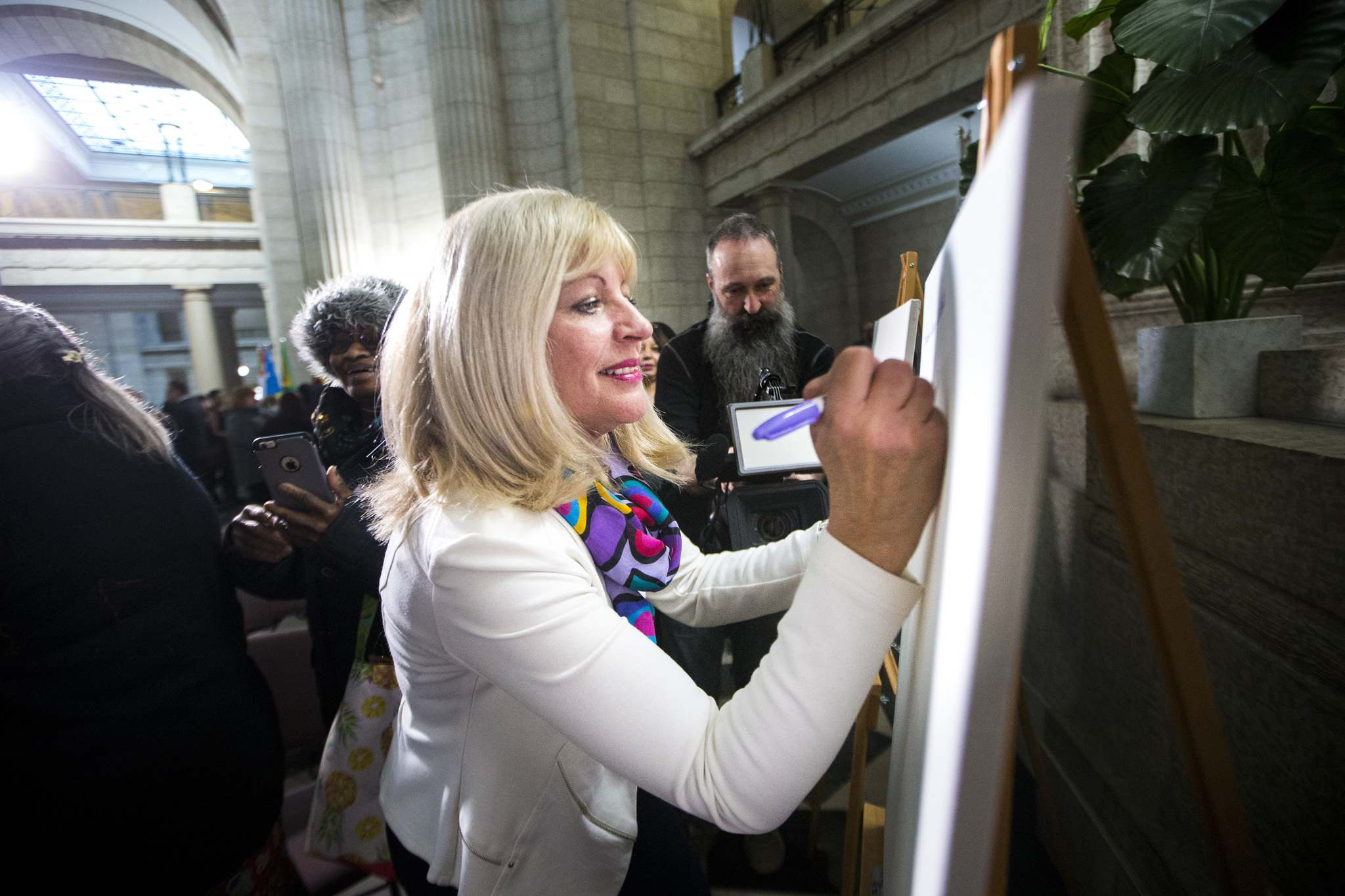 <p>Cathy Cox writes the name of a woman who inspires her (her Baba) on a canvas at the Manitoba Legislative Monday.</p>
