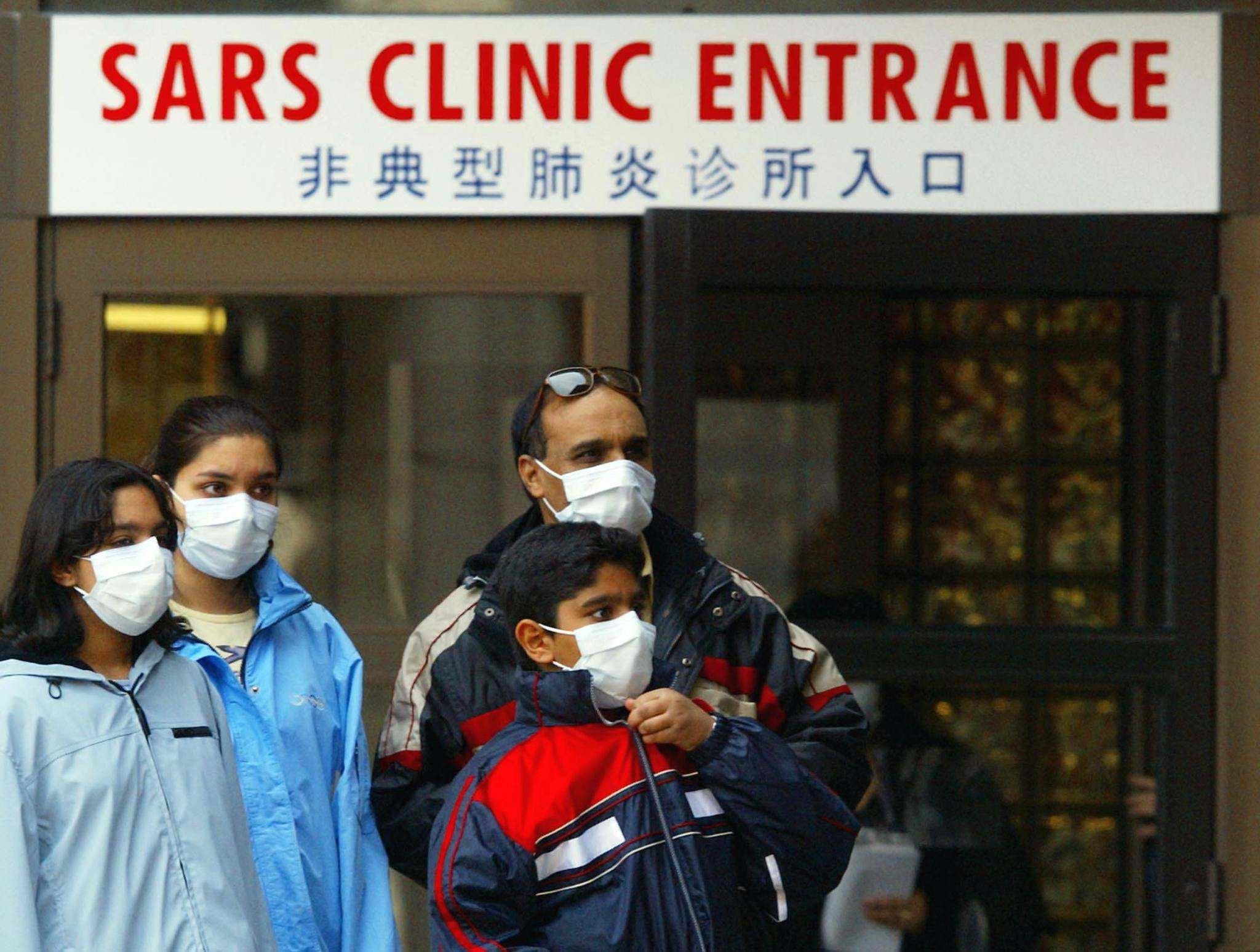 A family wears protective masks as they leave a SARS clinic in Toronto in March 2003. SARS brought the importance of public health funding to the forefront but it wasn't until after the H1N1 pandemic in 2009 that provinces committed to do more to fund public health — and many have since cut back on that spending.</p></p>