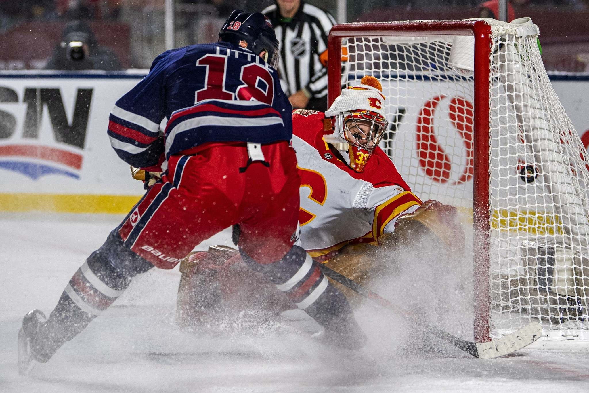 """<p>Winnipeg Jets' Bryan Little tips in the game-winning goal past Calgary Flames' goaltender David Rittich in overtime of the 2019 Heritage Classic in Regina.""""> </a><figcaption readability="""