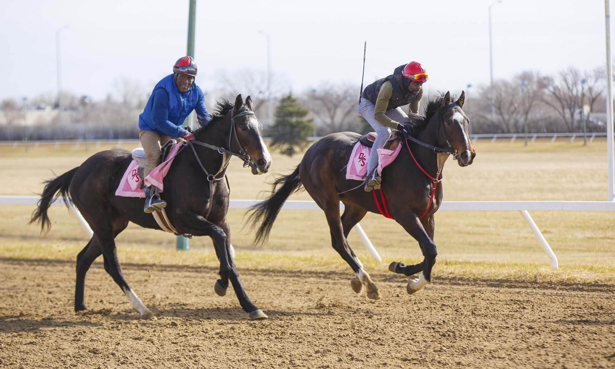 Sidney Blackwood (left) and Antonio Whitehall take their horses for their daily workout Thursday morning at Assiniboia Downs.