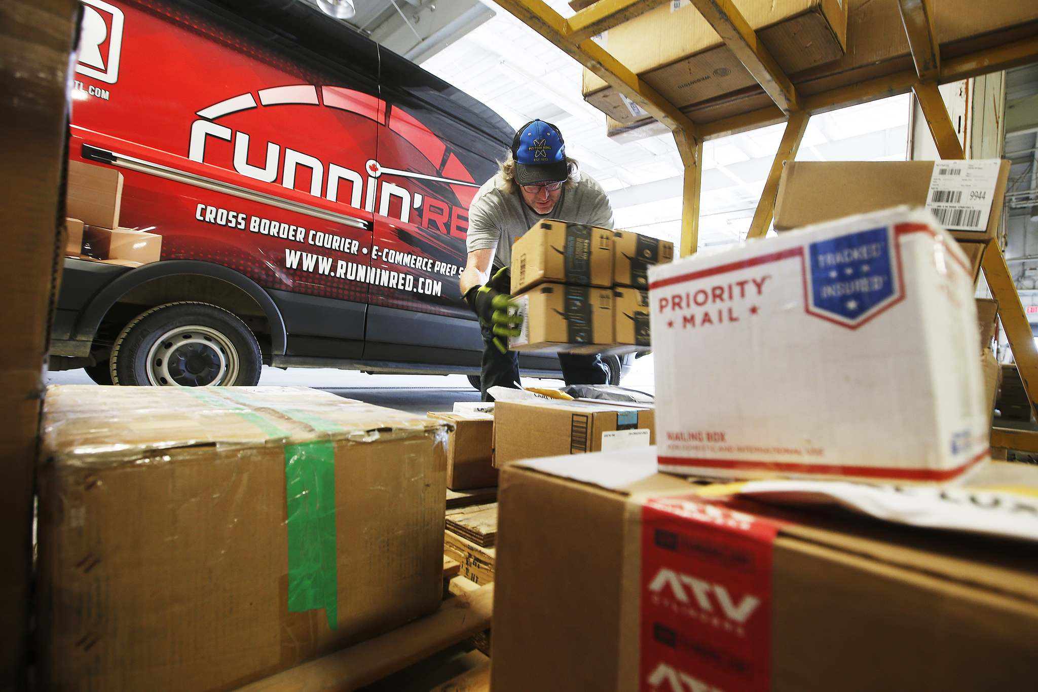 JOHN WOODS / WINNIPEG FREE PRESS</p><p>Mike Caners of Runnin' Red, a cross-border courier, unloads packages from Emerson in their warehouse. Runnin' Red co-owner Trevor Froese says that currently they are probably doing four to five times the normal volume.</p>