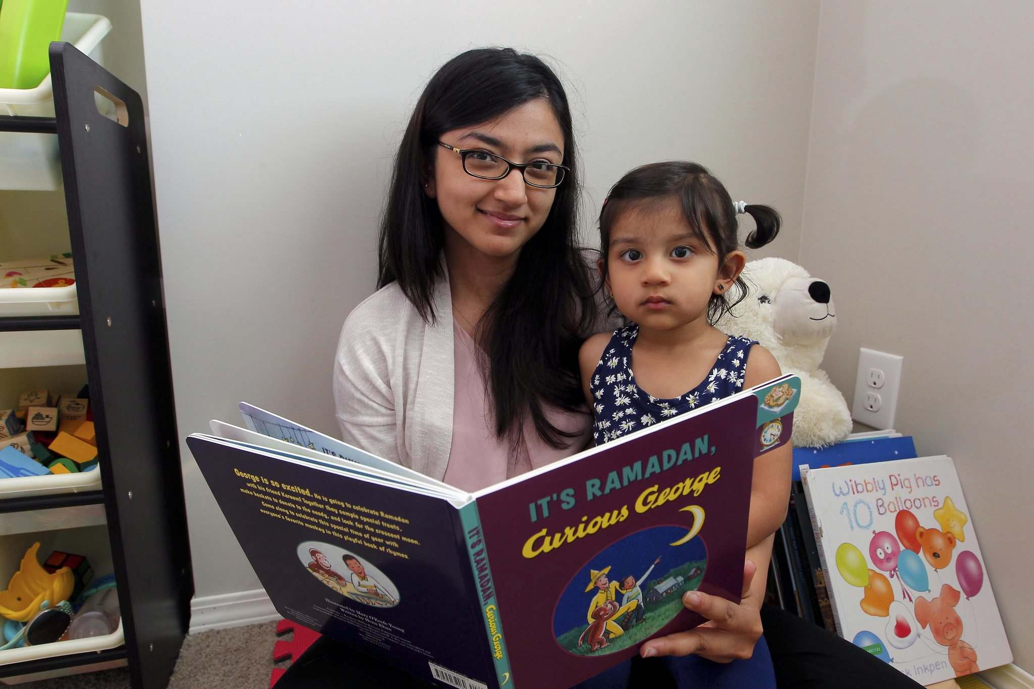 BORIS MINKEVICH / WINNIPEG FREE PRESS</p><p>Mother Taj Shakir-Farooqui and her daughter Zoya, 2, read the new Curious George book <em>It&#39;s Ramadan, Curious George</em>, which employs the familiar children&#39;s book character to help explain the rituals of Islam&#39;s holiest month.</p></p>