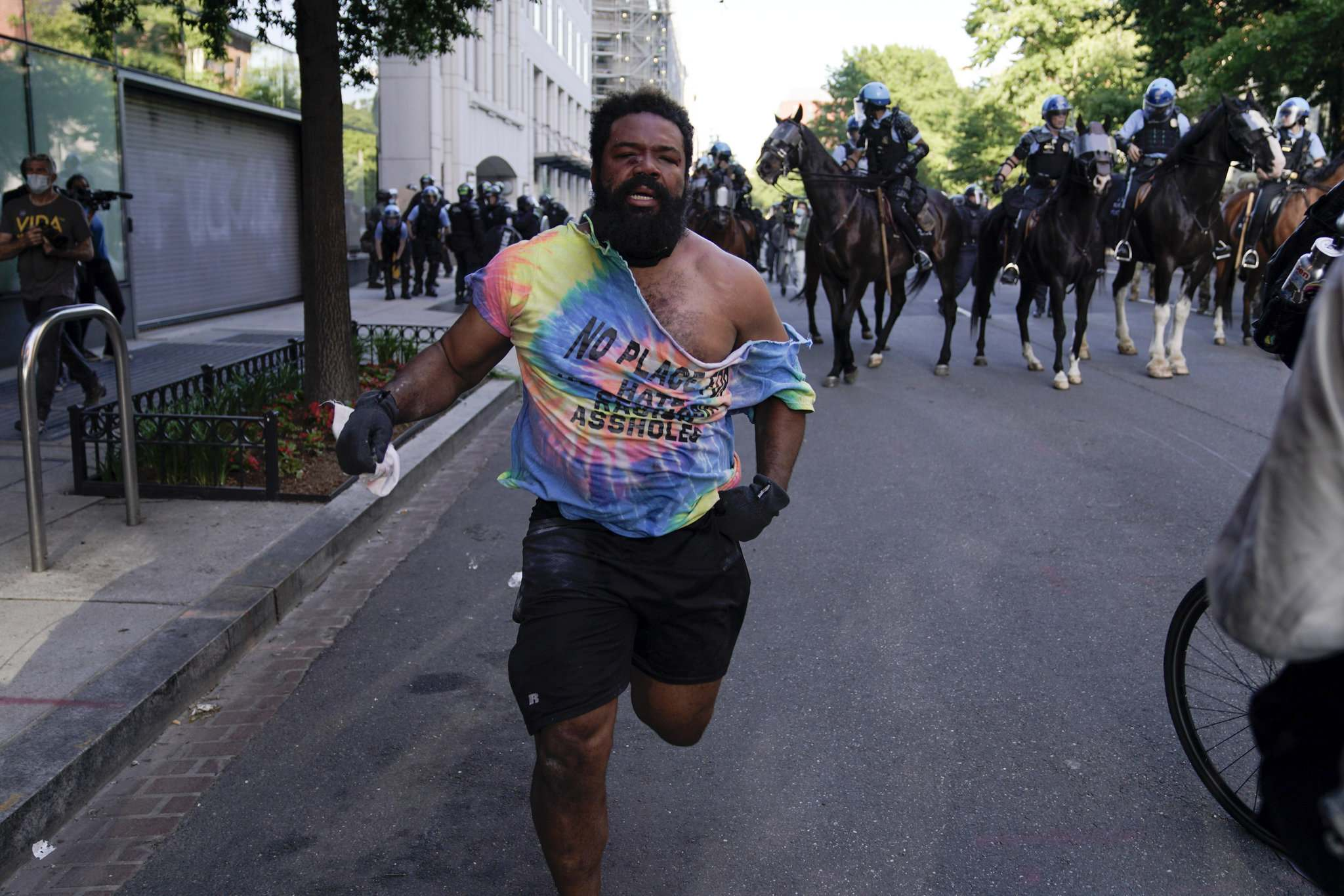 A demonstrator and others who gathered to protest the death of Floyd Monday move away from police officers on horses near the White House in Washington.