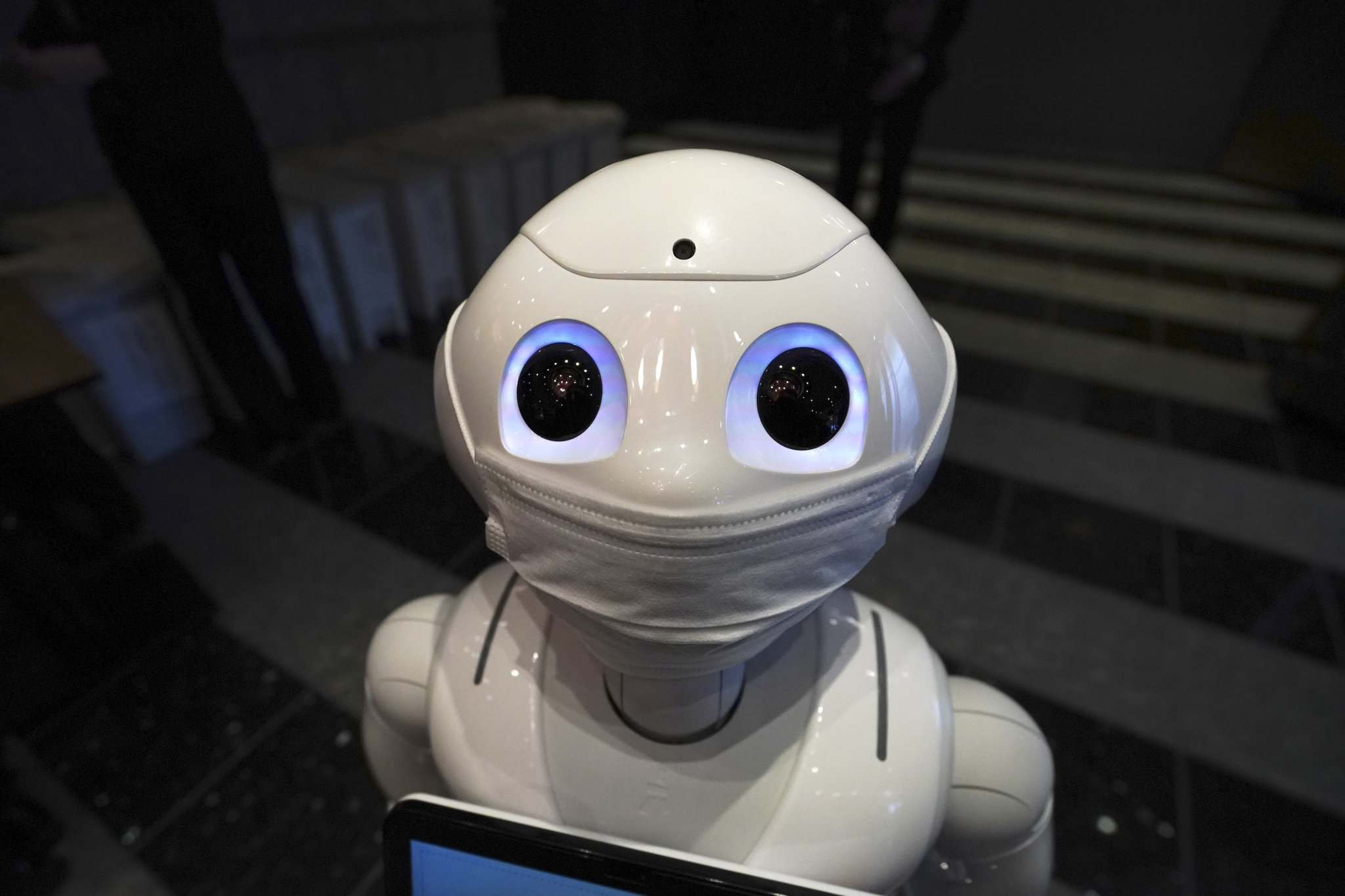 Eugene Hoshiko / The Associated Press</p><p>A humanoid robot, Pepper, with a face mask is placed at the door at the lobby of a hotel for new COVID-19 patients with mild symptoms during a media preview in Tokyo.</p>