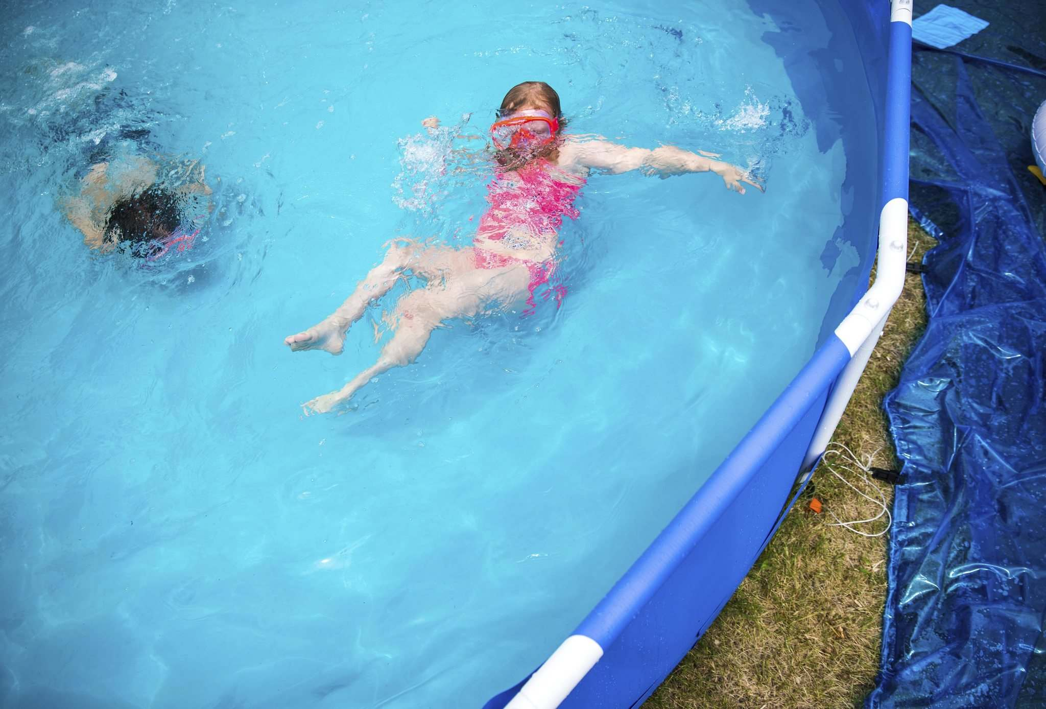 Julie Kay and her brother Liam enjoy an afternoon playing in their recently installed above-ground pool. (Mikaela MacKenzie / Winnipeg Free Press)