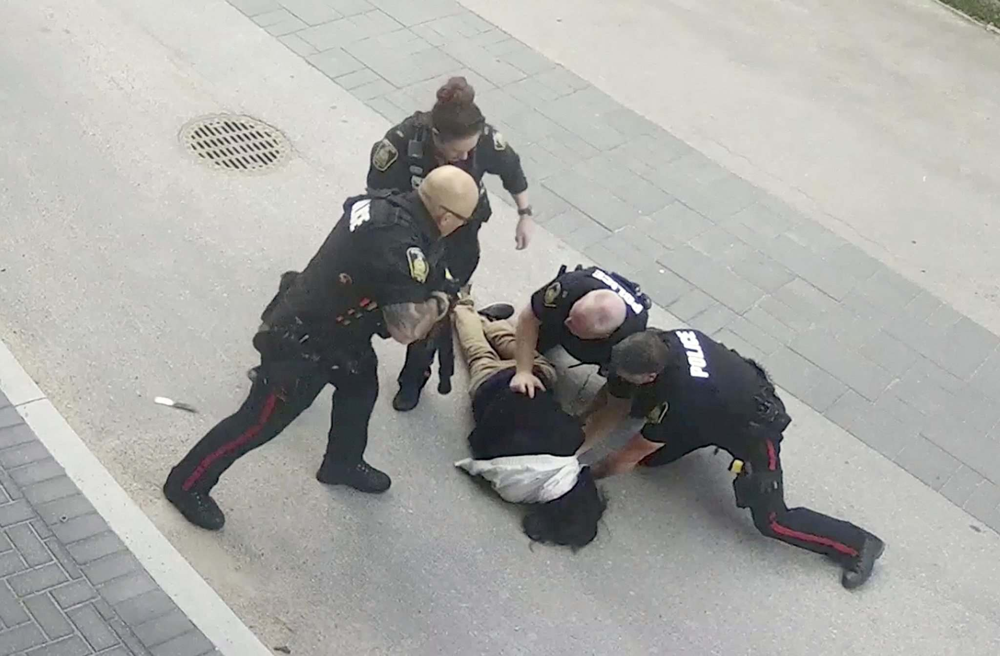 Police were criticized for using too much forced during Thursday's arrest of this suspect. A knife is dislodged from the man (seen on road left of officer) during the takedown. (Winnipeg Free Press)