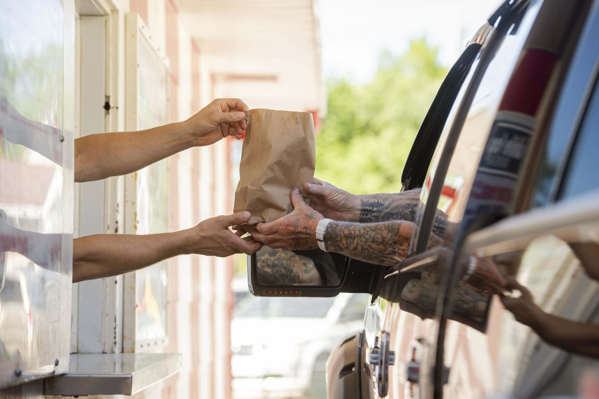 Mike Sudoma / Winnipeg Free Press</p><p>White Top Drive In owner Demos Louizos hands an order to a customer through the busy drive-thru window at the Manitoba Avenue burger joint.</p>