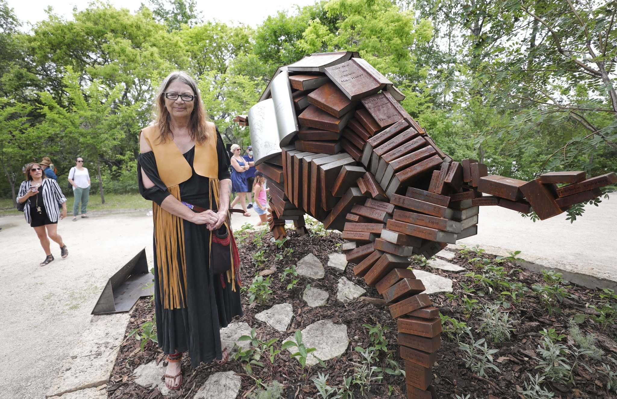 RUTH BONNEVILLE / WINNIPEG FREE PRESS</p><p>Local artist Val Vint with her new piece, Education is the New Bison, a 12-foot bison made up of 200 steel replicas of books and other articles. Each book is written by an Indigenous or allied author, most of whom are local.</p></p>