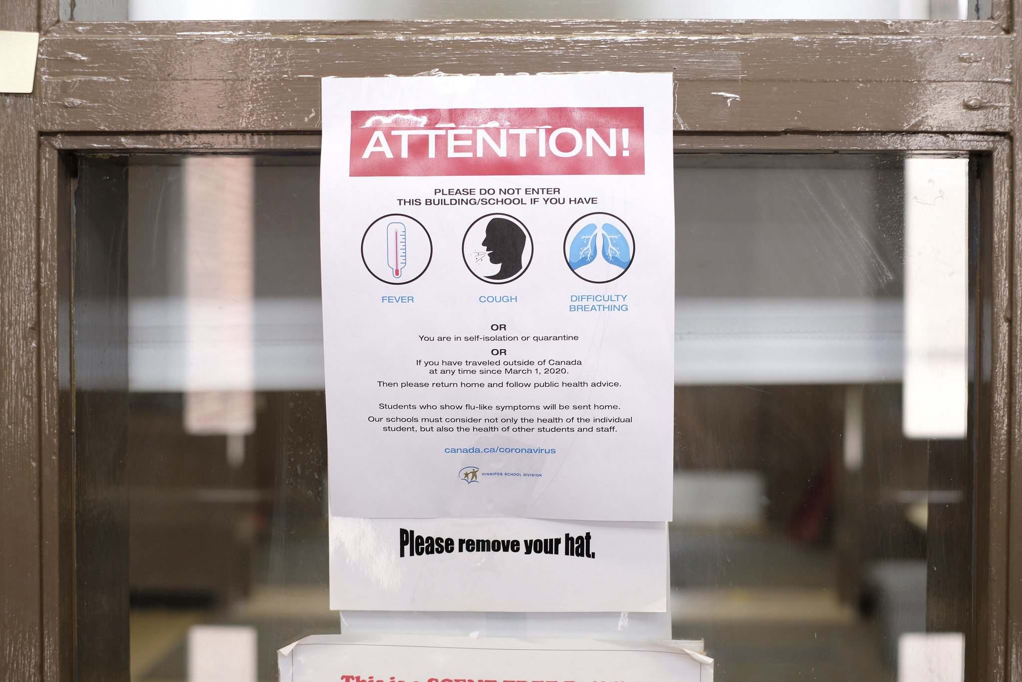 A poster advises of COVID-19 restrictions at Lord Nelson School. (Shannon VanRaes / Winnipeg Free Press)