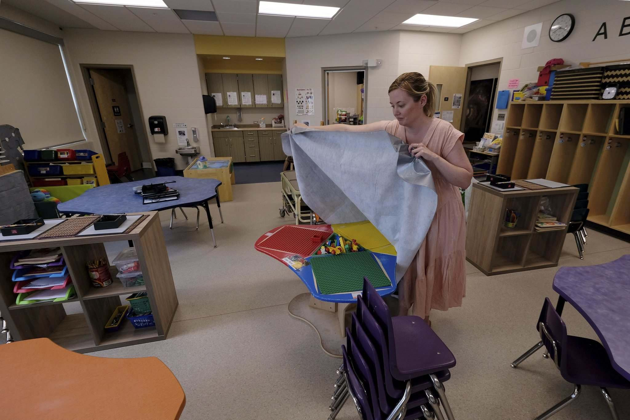 Kindergarten teacher, Kristy Frohwerk, prepares her classroom at Lord Nelson School for the eventual return of students by covering up a LEGO table on June 25, 2020. (Shannon VanRaes / Winnipeg Free Press)