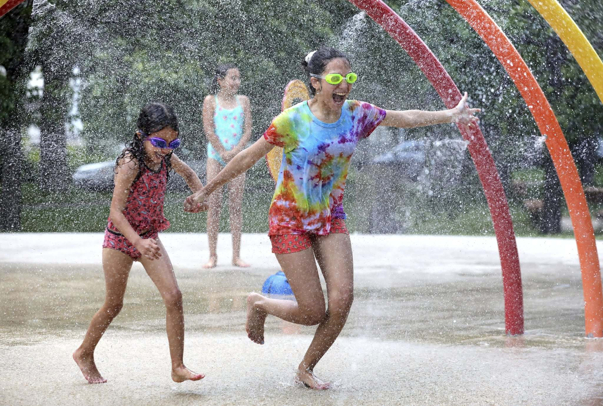 Sisters Maylis, 12, and Melanie, 7, enjoy cooling themselves at Provencher Park Spray Pad Monday.