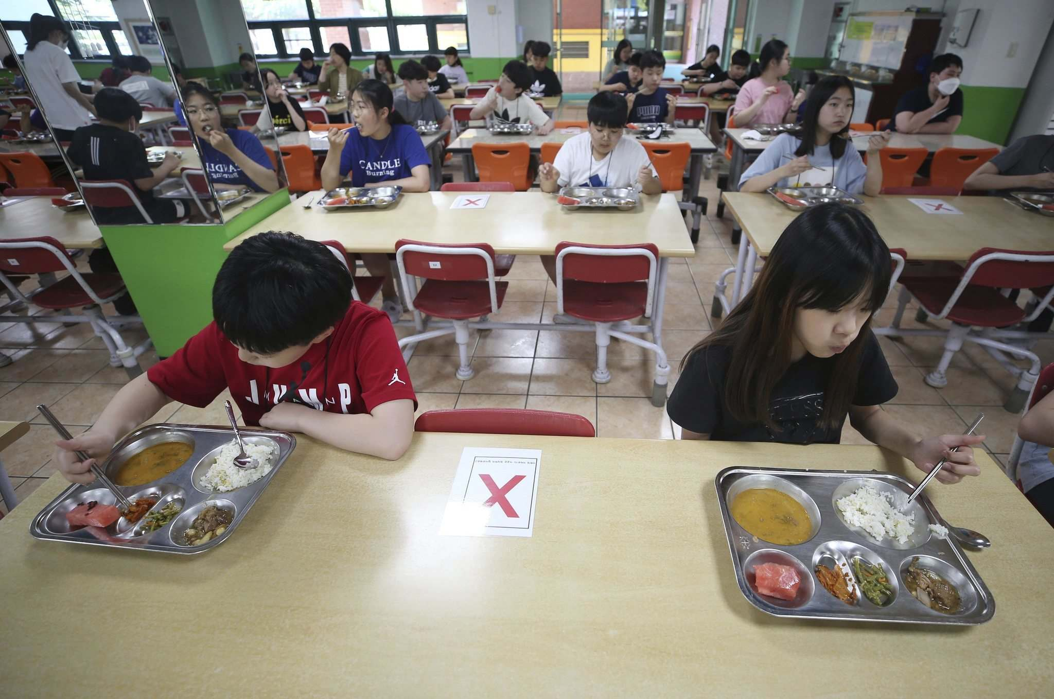 Elementary school students eat lunch while keeping their distance from each other at the cafeteria of their school in Gwangju, South Korea, last month. (Cheon Jeong-in / Associated Press files)