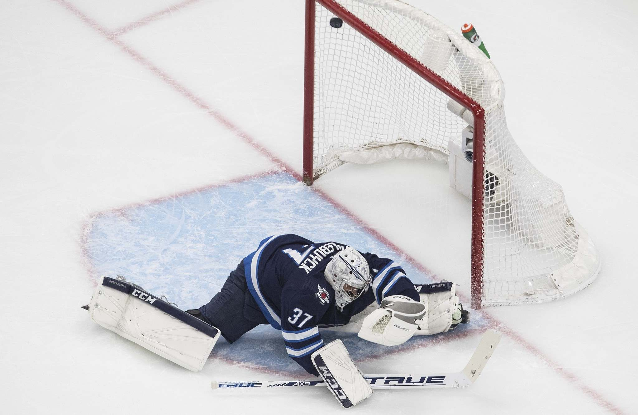 The puck hits the post behind Connor Hellebuyck during the first period Tuesday.