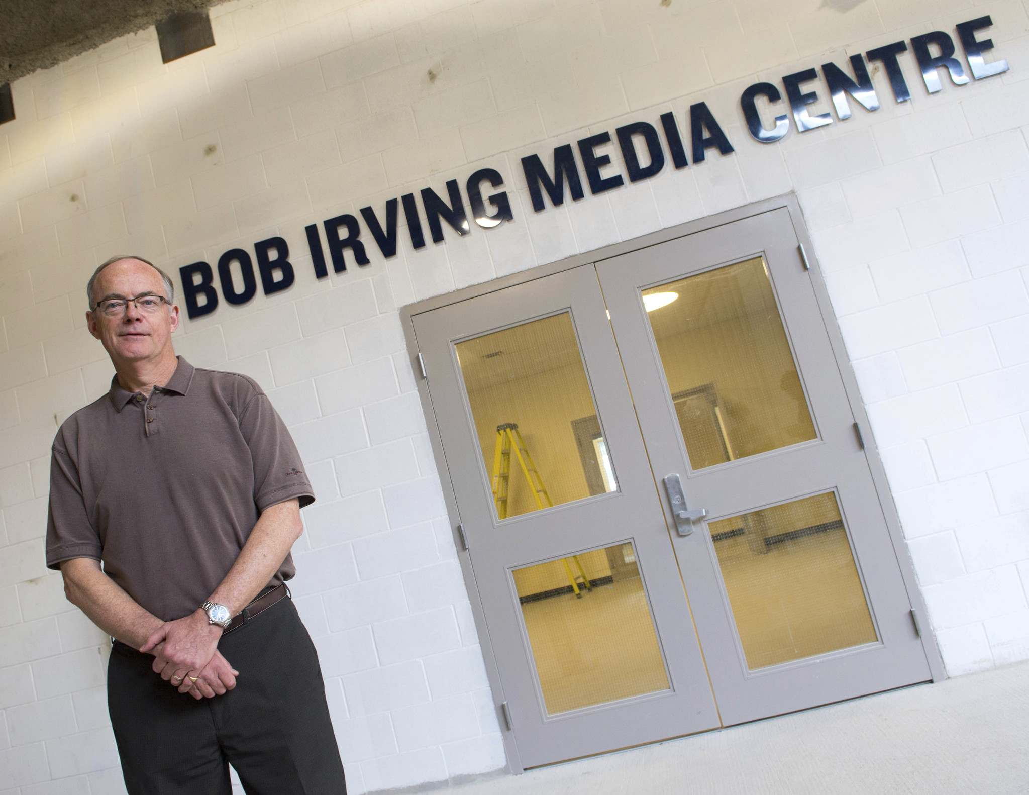 Irving stands in front of the doors leading into the Bob Irving Media Centre, which was named after the long-time broadcaster when Winnipeg's new stadium opened in 2013.