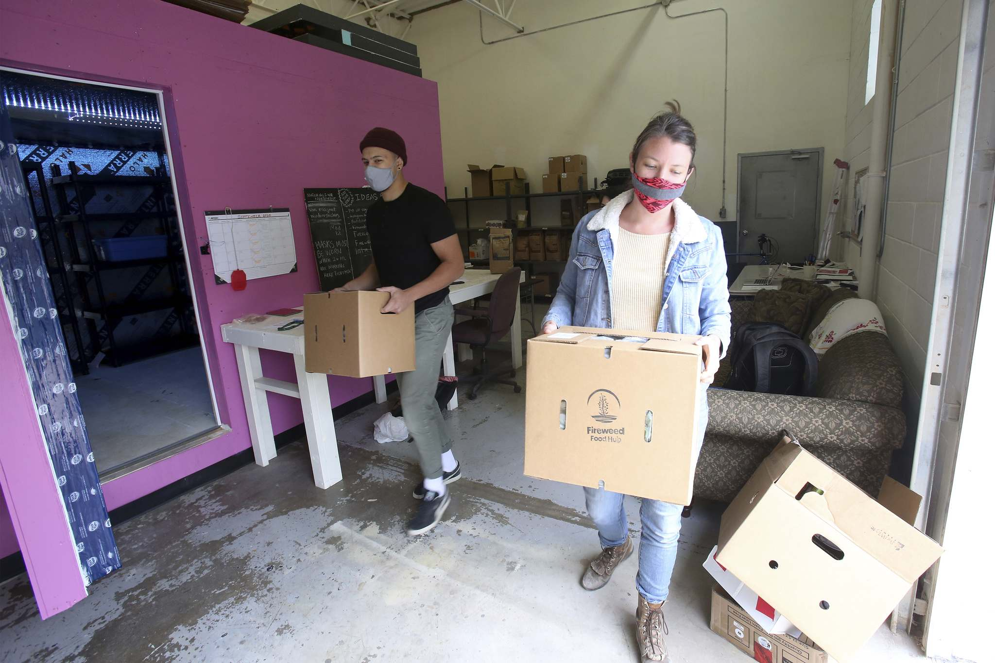 Anna Sigrithur and Conor Nedelec at the Fireweed Food Co-Op's food hub's warehouse on Clifton Street. (Shannon VanRaes / Winnipeg Free Press)