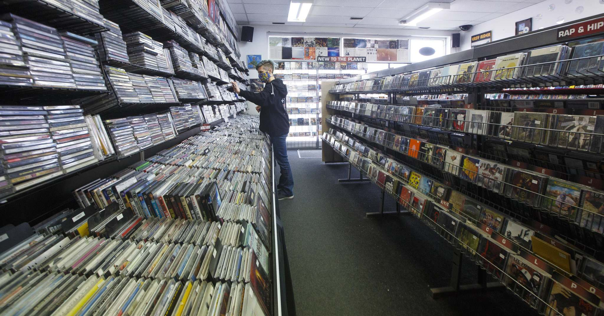 Store manager Cathie Stankey organizes some CDs. (Mike Deal / Winnipeg Free Press)</p>