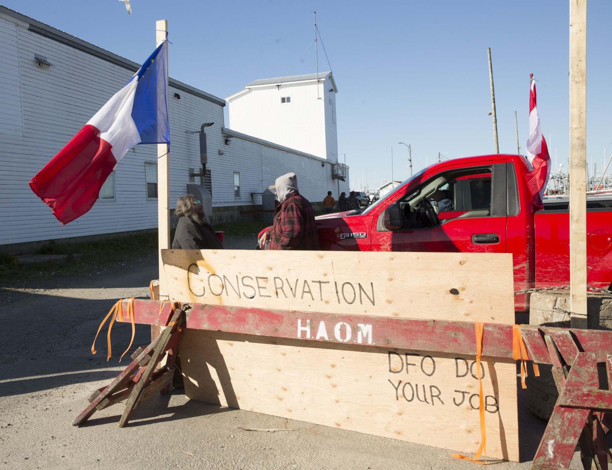 Fishers stand at a barricade in Meteghan, N.S., on Sunday. A spokesman said about 100 boats were removing Indigenous lobster traps and fishers were intending to take them to the wharf in Meteghan later in the day.</p></p>