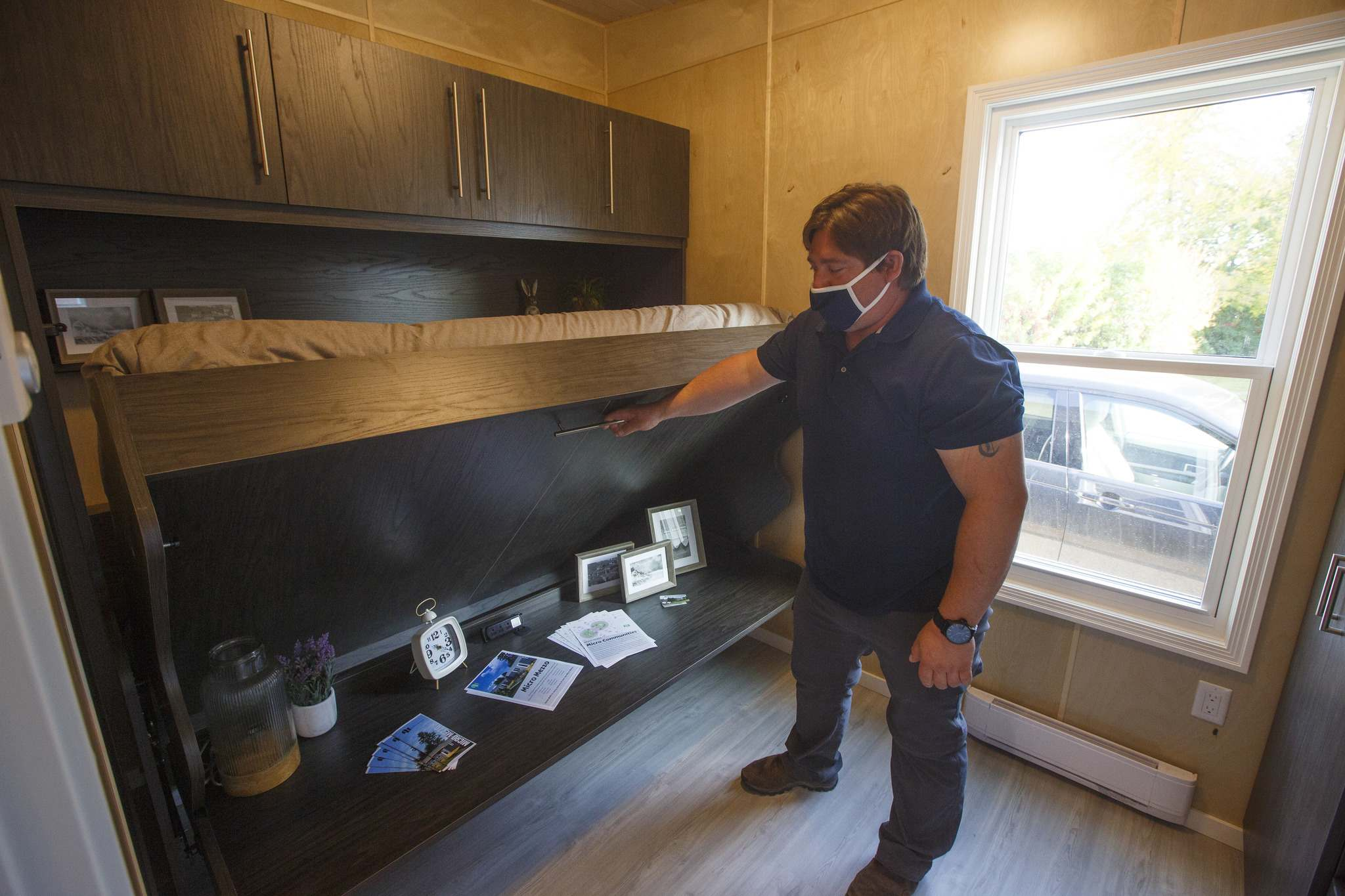 Jason Vitt pulls down the optional hidden bed/desk in the bedroom of the 379sqft Micro Mezzo that Mezzo Homes produce in their construction facility in Selkirk. (Mike Deal / Winnipeg Free Press)