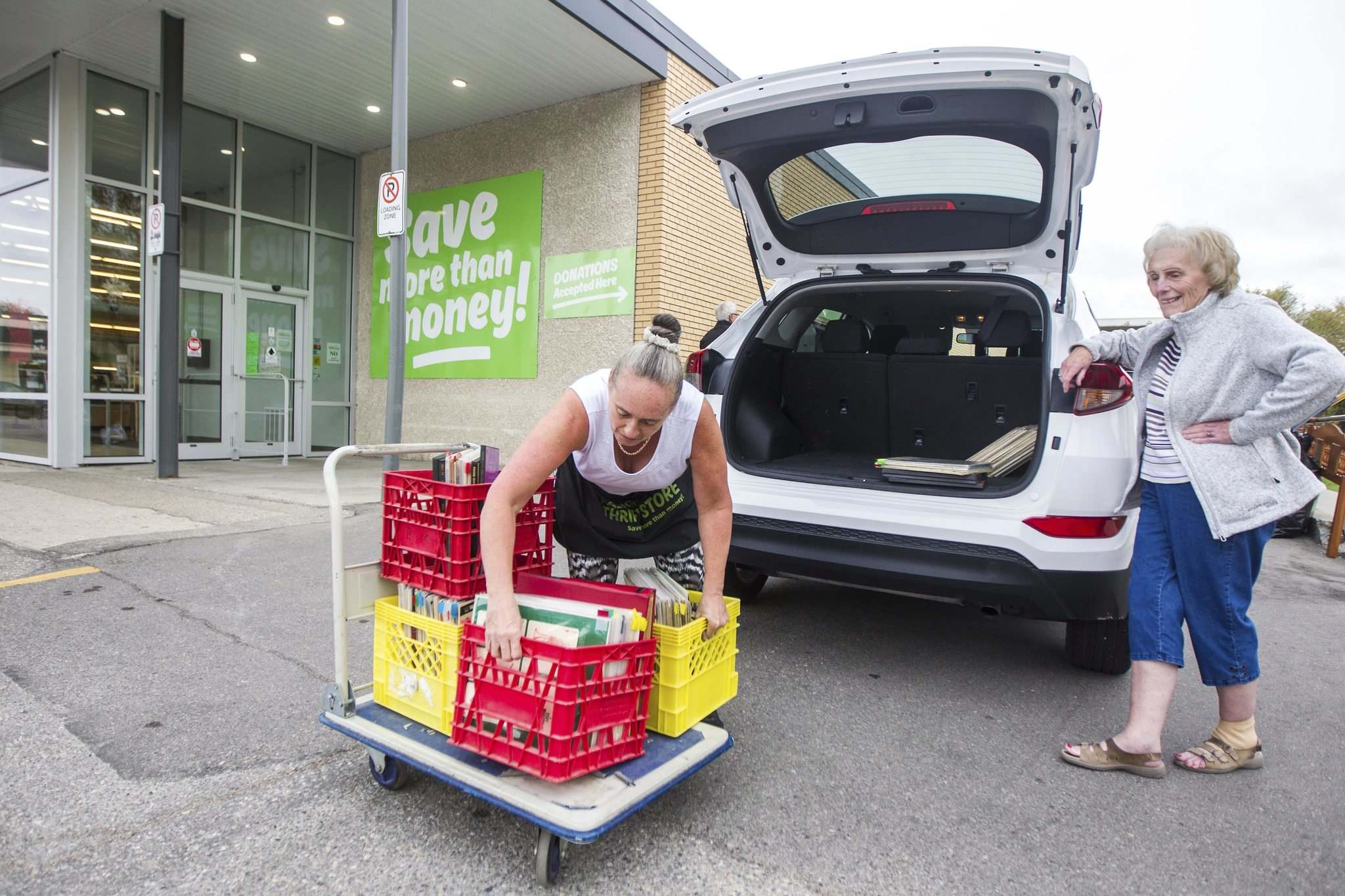 Receiver Alison Seavers (left) unloads donations from Monique Bessems' car at the Mission Thrift Store. (Mikaela MacKenzie / Winnipeg Free Press)