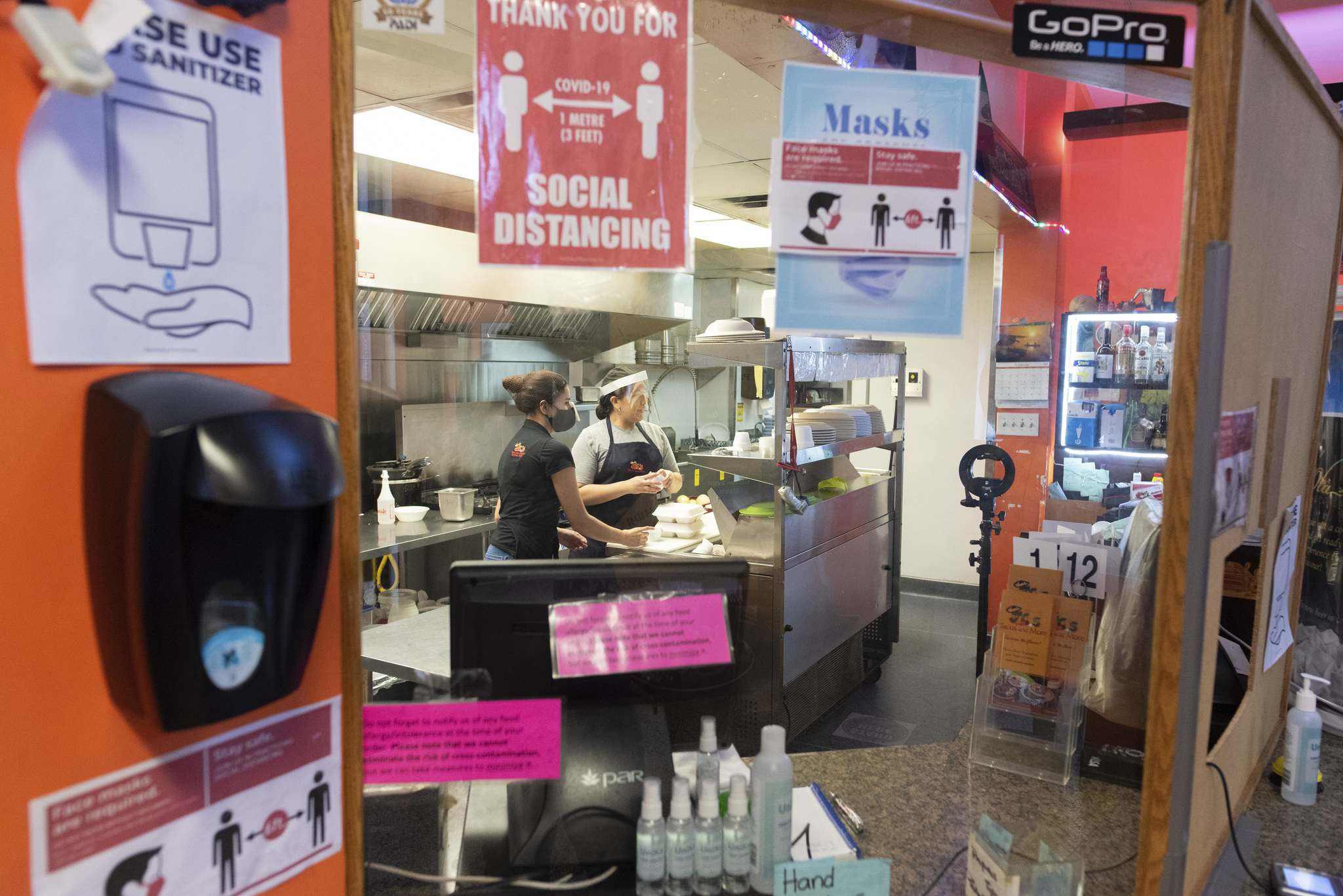 JESSE BOILY / WINNIPEG FREE PRESS</p><p>Angie Lozano, left, and Paola Ariza prepare an order for takeout behind a plexiglass barrier at JC's Tacos and More on Thursday. Restaurants such as JC's Tacos and More have spent big money on safety equipment for preventing the spread of COVID-19.</p>