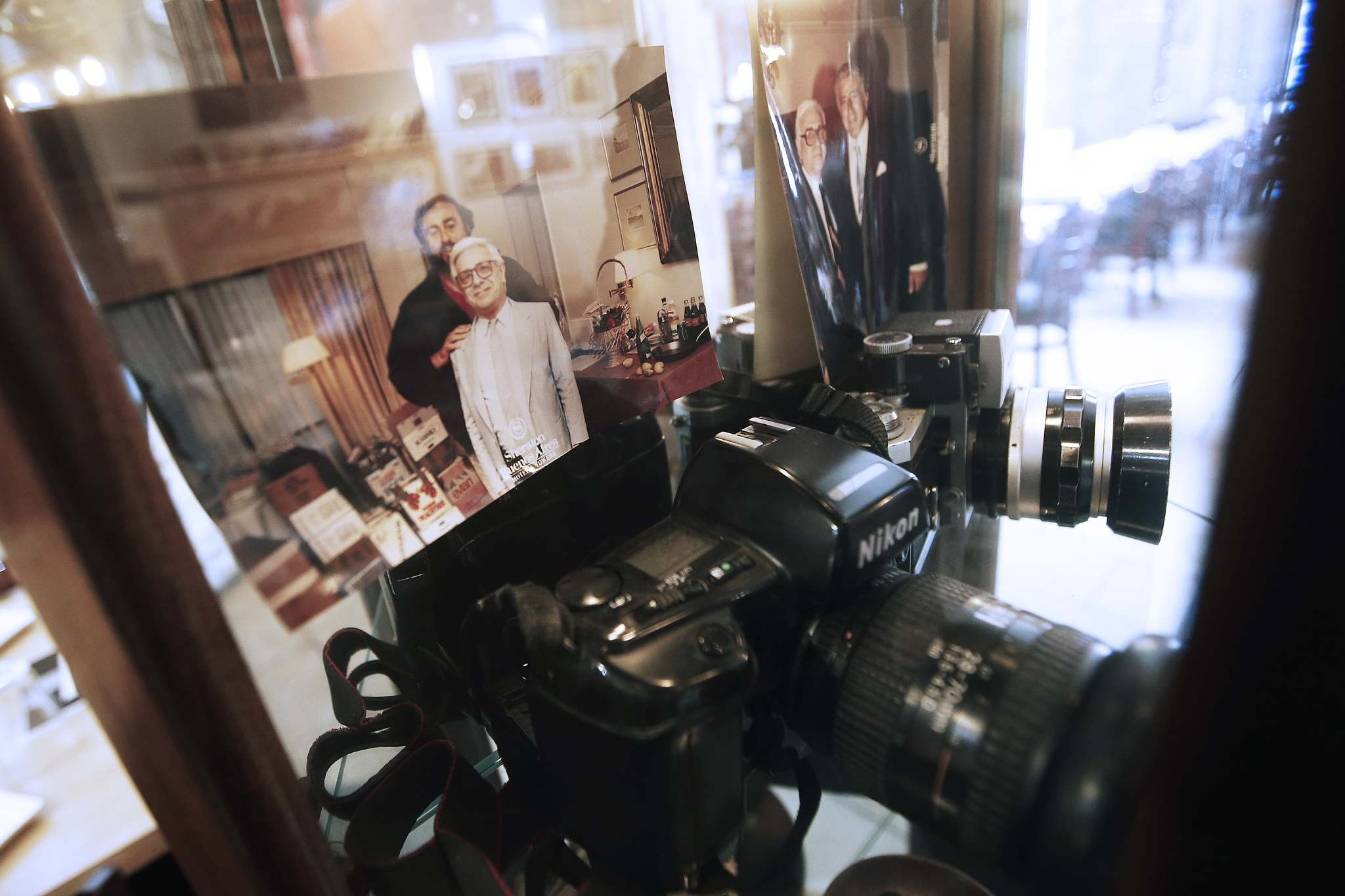 Photos on display in a cabinet at Alfonso Maury's pizzeria include images of his father, Hector, with Pavorratti and Tony Bennett beside his father's cameras. (John Woods / Winnipeg Free Press)</p></p>