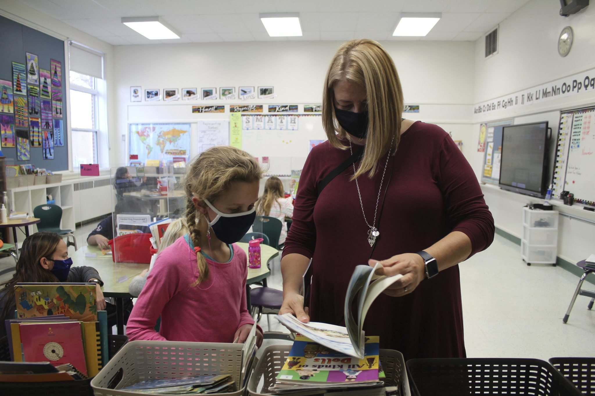 Grade 3/4 teacher at Governor Semple School, Shelley Torz, looks at a book with student, Chloe.