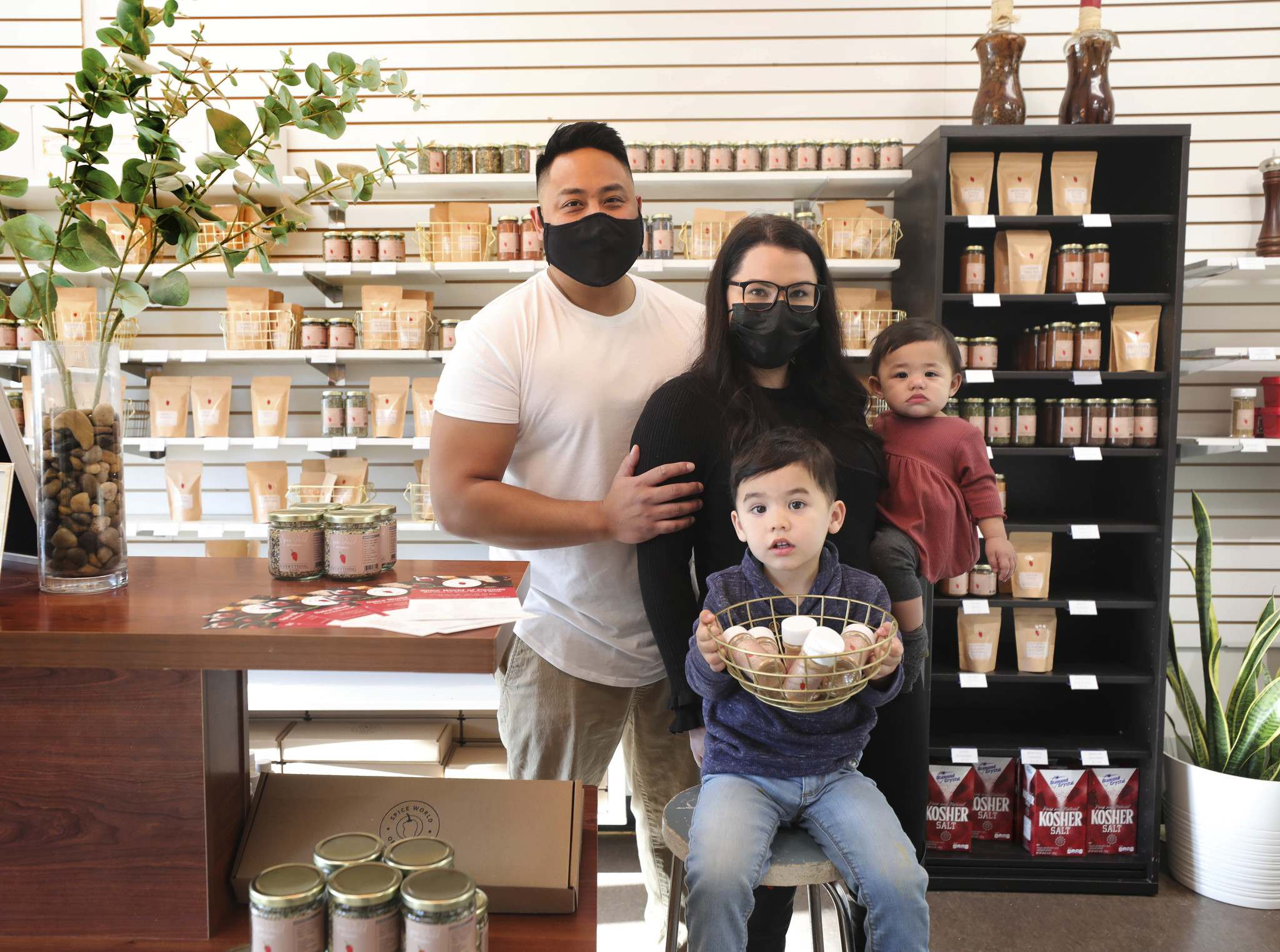 RUTH BONNEVILLE / WINNIPEG FREE PRESS</p><p>Spice World owners Aaron Delos Santos, his wife Madilyn and children Jude, 2 and Emme, 9 months, have been making homemade spice blends at their store on Marion Street since 1997.</p>