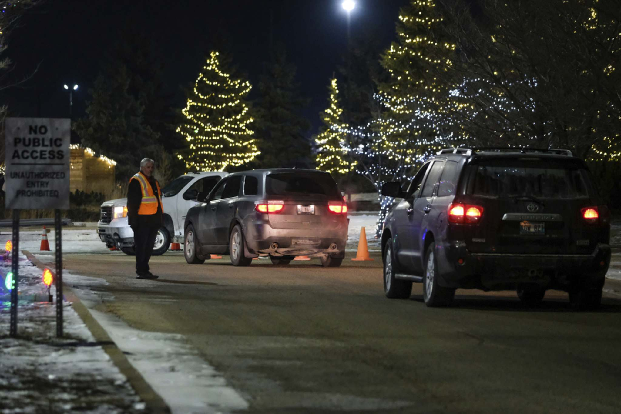 Daniel Crump / Winnipeg Free Press</p><p>Church Springs private security stands guard as vehicles line up to attend a drive-in church service on Saturday.</p>