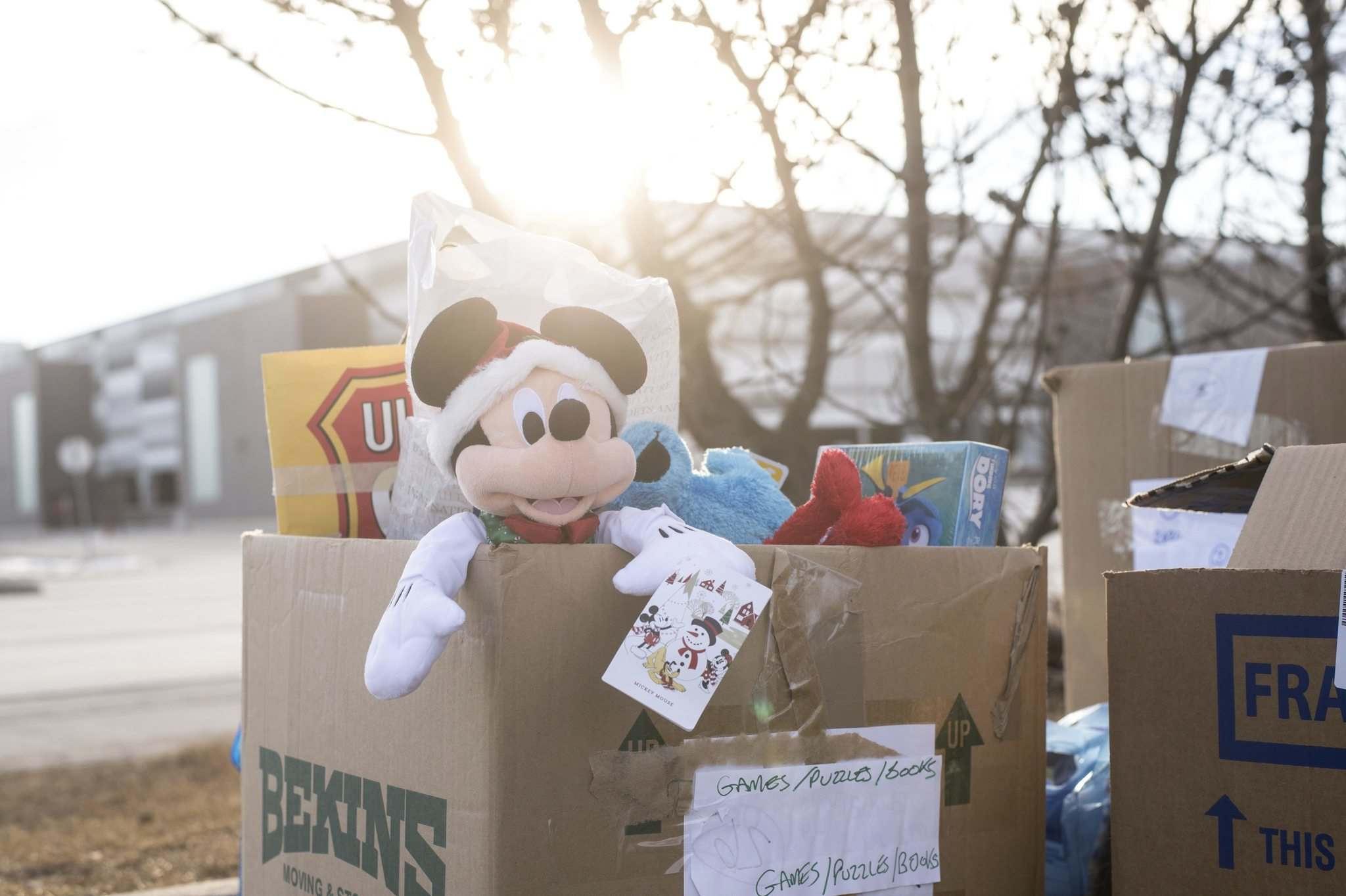 A stuffed Mickey Mouse doll sticks out of a box of toy donations for the Salvation Army's Toy Mountain drive in the Toys' R Us parking lot on Friday. (Mike Sudoma / Winnipeg Free Press)