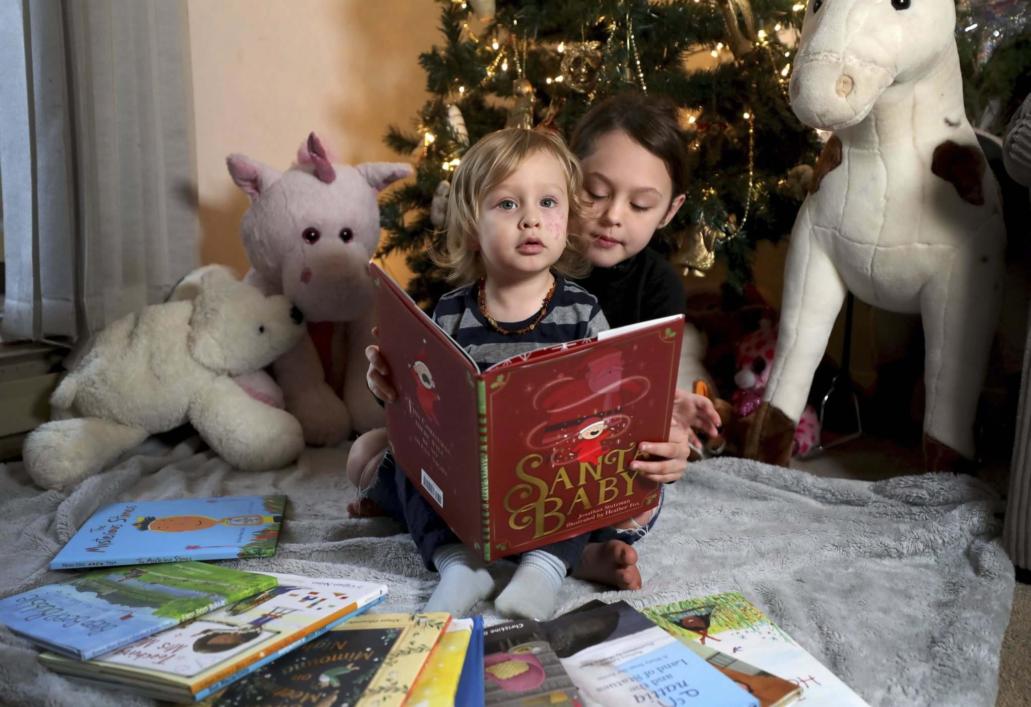 RUTH BONNEVILLE / WINNIPEG FREE PRESS</p><p>Winter Wright (8) and her little brother Gabriel (18 months) read Santa Baby, written by Jonathan Stutzman and illustrated by Heather Fox, under their Christmas tree last week.</p>