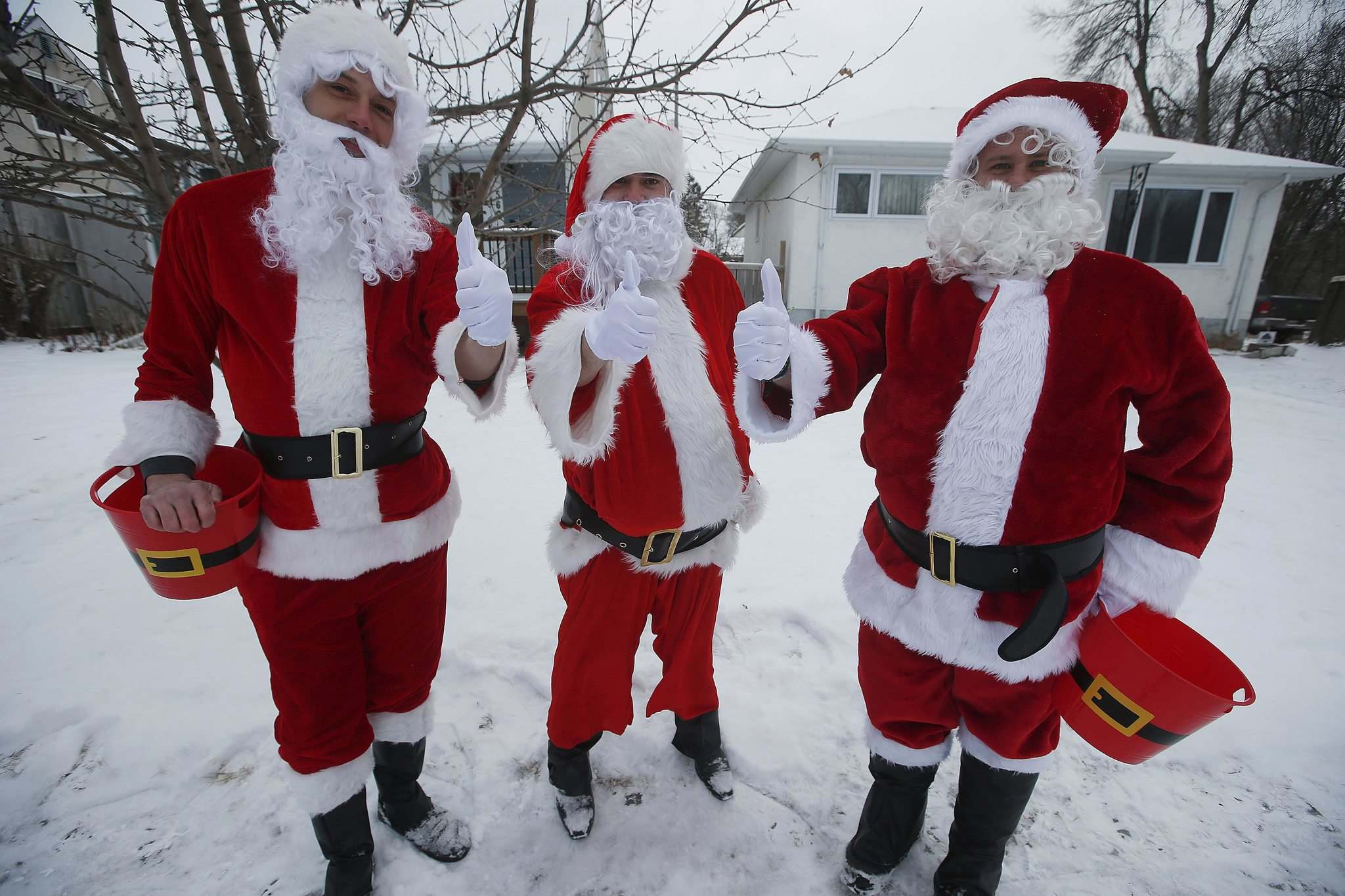 JOHN WOODS / WINNIPEG FREE PRESSMichael Cheetham, from left, Jason Gray and Lee Jacobson dress as Santa and go around visiting children outside their homes Sunday, December 13, 2020. The friends are collecting food for Harvest Manitoba.</p>