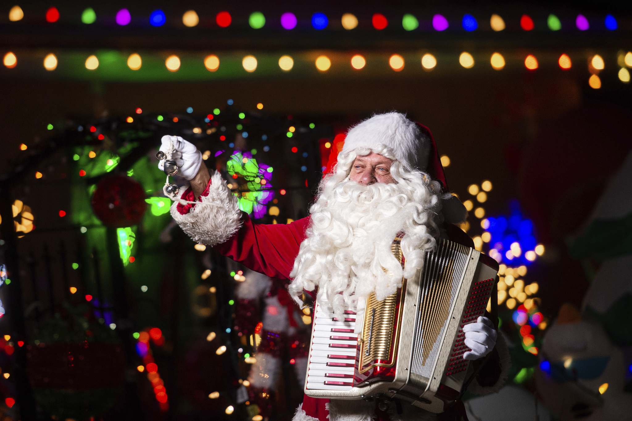 Stan Bedernjak spreads holiday cheer with his accordion in front of a brightly decorated house on Lincrest Road last week.