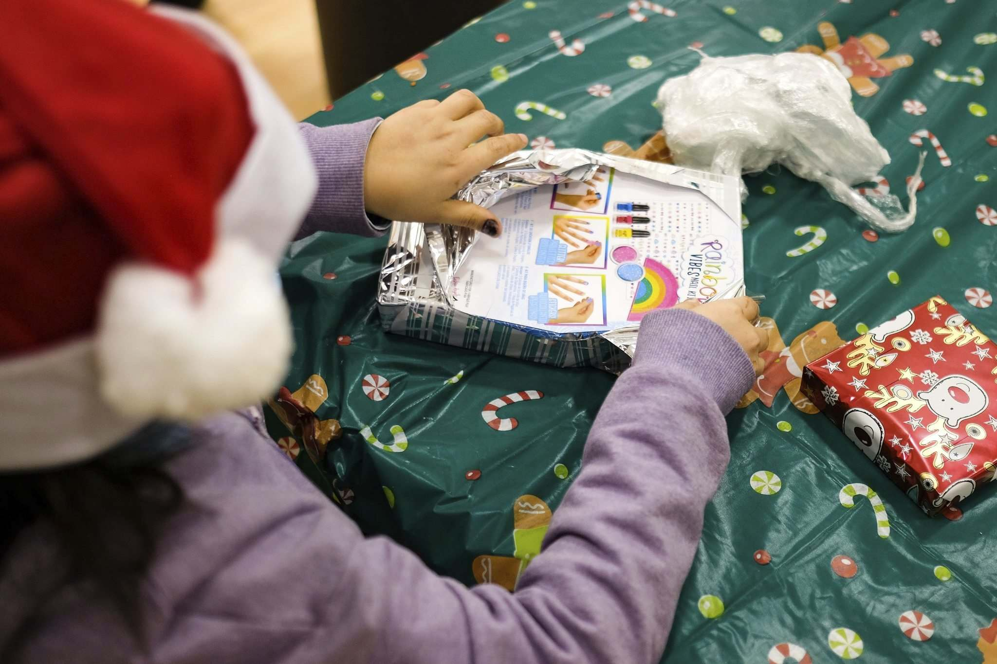 A child finishes unwrapping a Christmas present as part of a game.