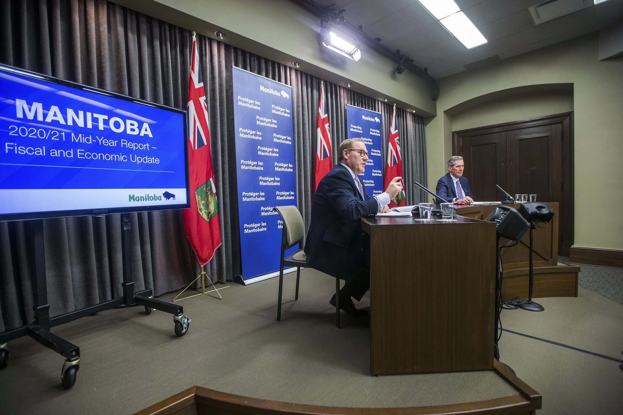 Finance minister Scott Fielding (left) and premier Brian Pallister give a mid-year financial update at the Manitoba Legislative Building in Winnipeg Thursday.