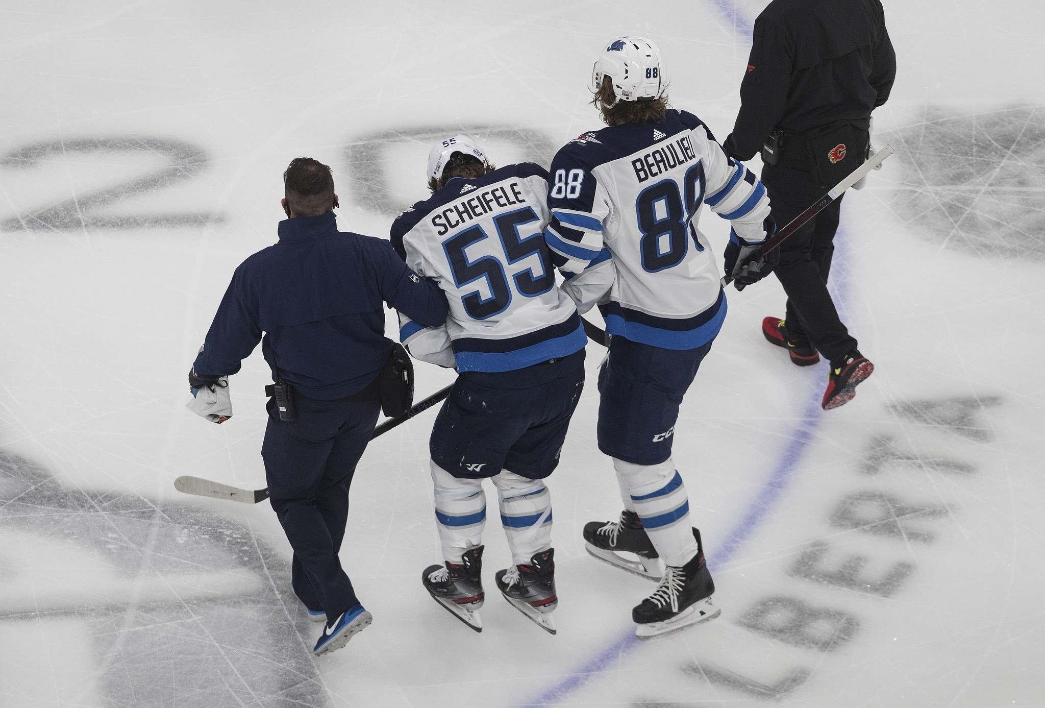 Mark Scheifele is helped off the ice after being injured against the Calgary Flames during the first period of a qualifying round game last summer.