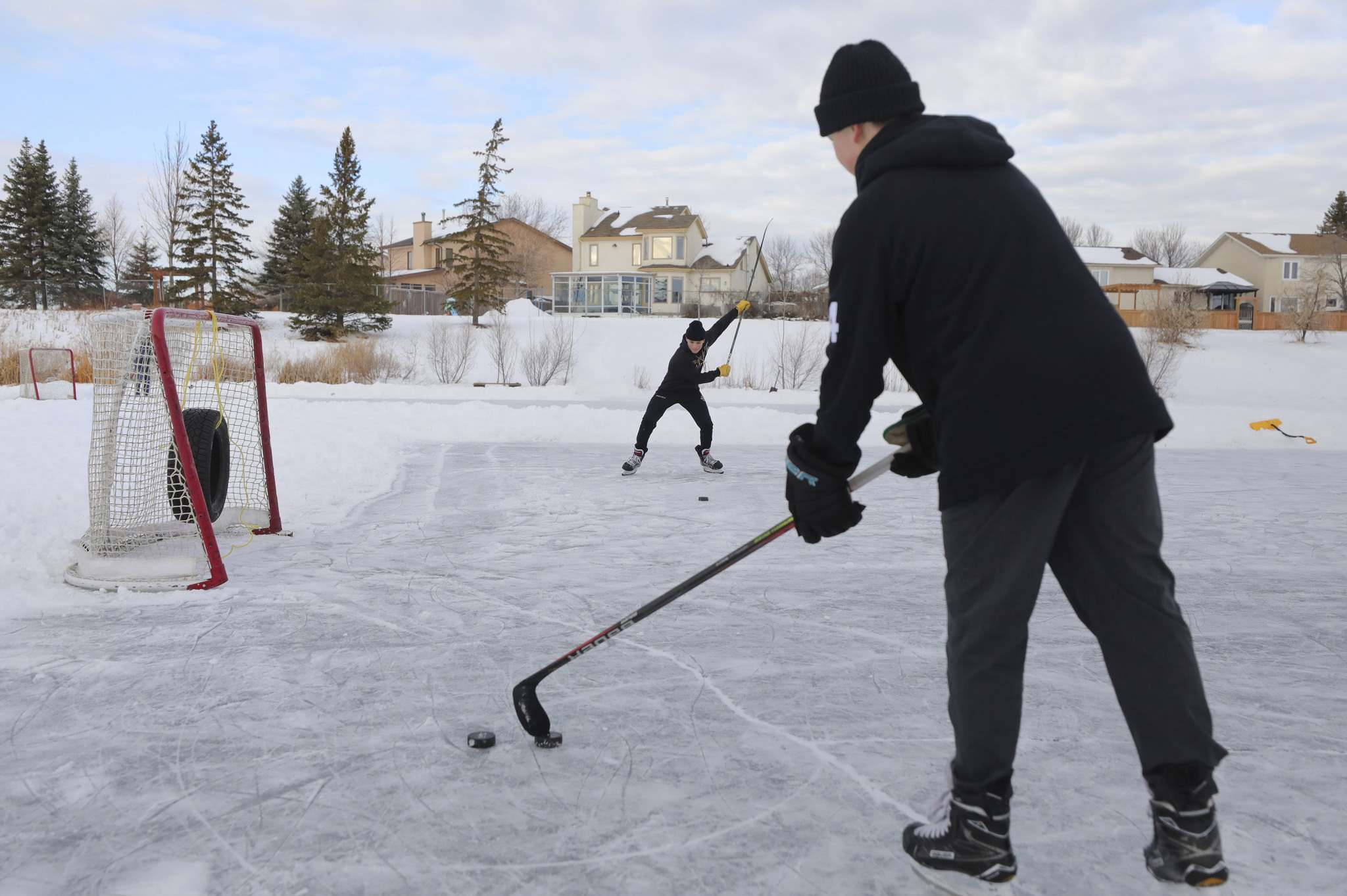 Two 14-year-old boys take shots at a net set up on a retention pond in St. Vital on Tuesday. Coun. Janice Lukes would like to see if more retention ponds can be used for skating. (Ruth Bonneville / Winnipeg Free Press)</p>