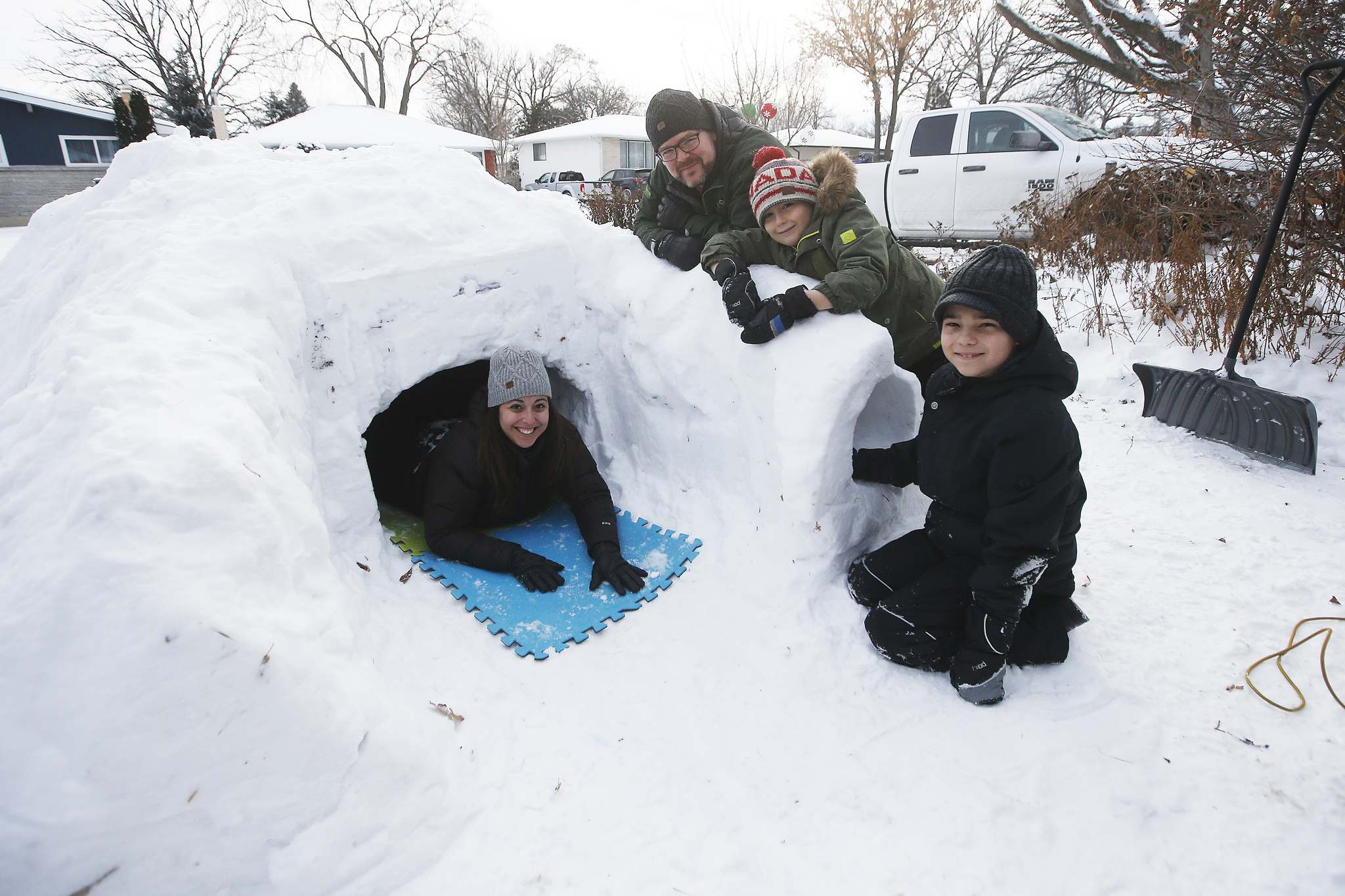 JOHN WOODS / WINNIPEG FREE PRESS</p><p>Brendan McManus and Marcela Cabezas work on their quinzee with sons Nate (right) and Kellan. Every winter since Nate was three, the family has built a snow shelter in their front yard.</p></p></p>