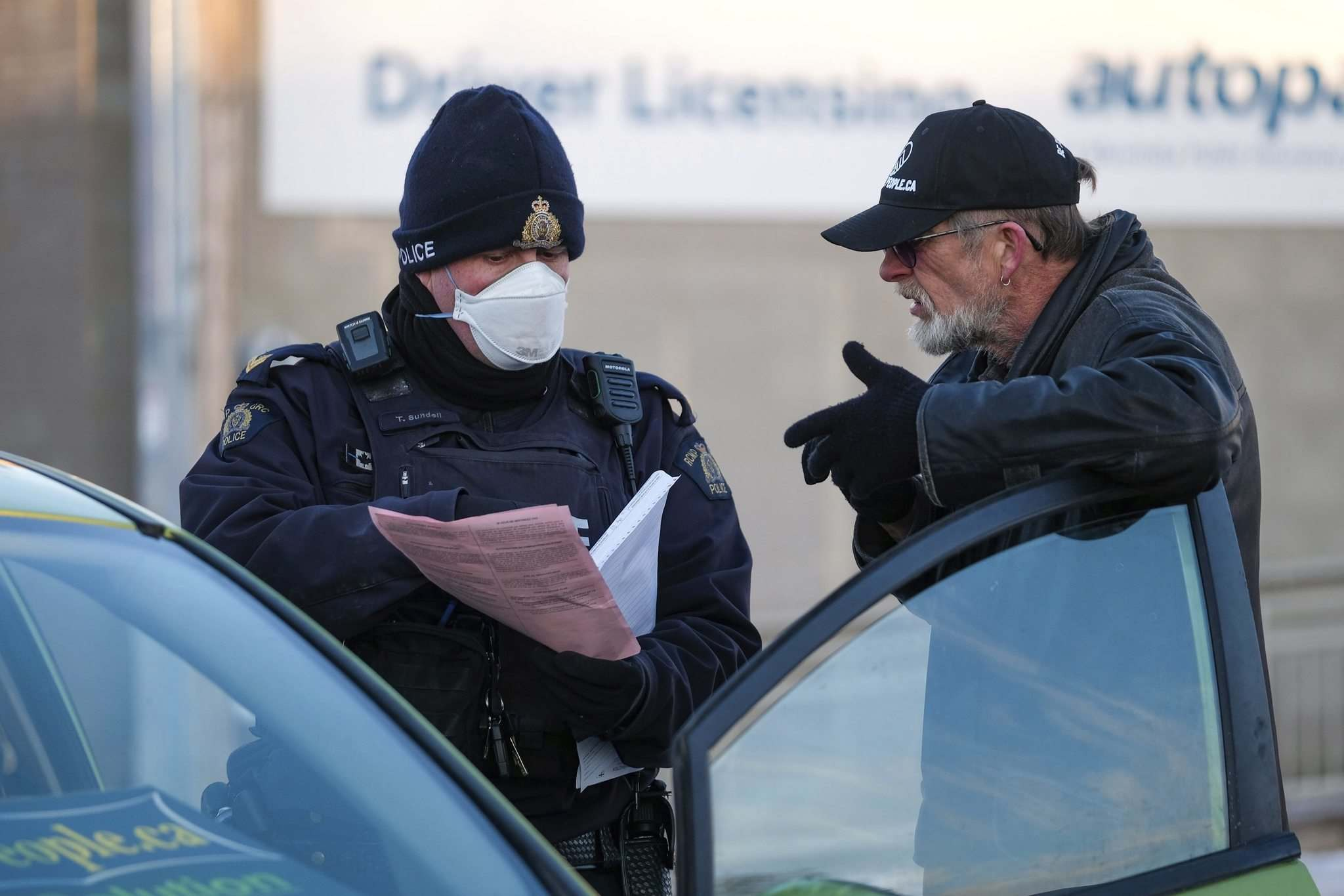 RCMP issue a ticket to a man who spoke at the protest. (Daniel Crump / Winnipeg Free Press)</p>