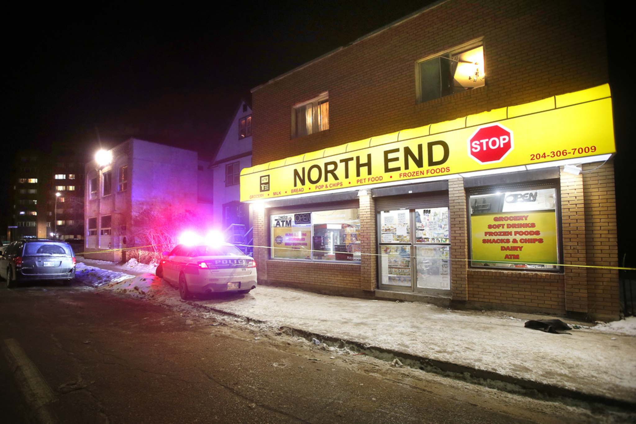 Police investigate on Selkirk Avenue in the North End on Monday evening. (John Woods / Winnipeg Free Press)</p>