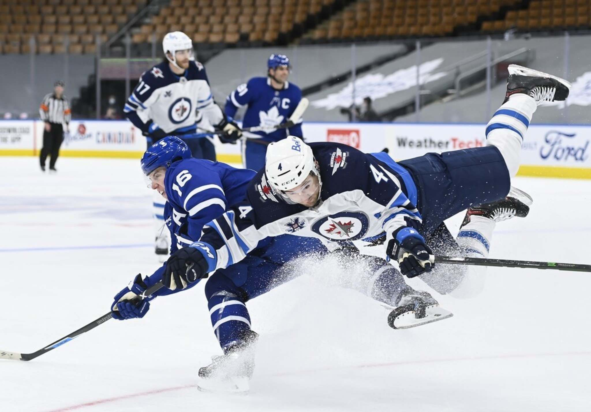 Toronto Maple Leafs right wing Mitchell Marner scores on an empty net and takes a hit from Winnipeg Jets defenceman Neal Pionk during third period NHL hockey action in Toronto on Monday.