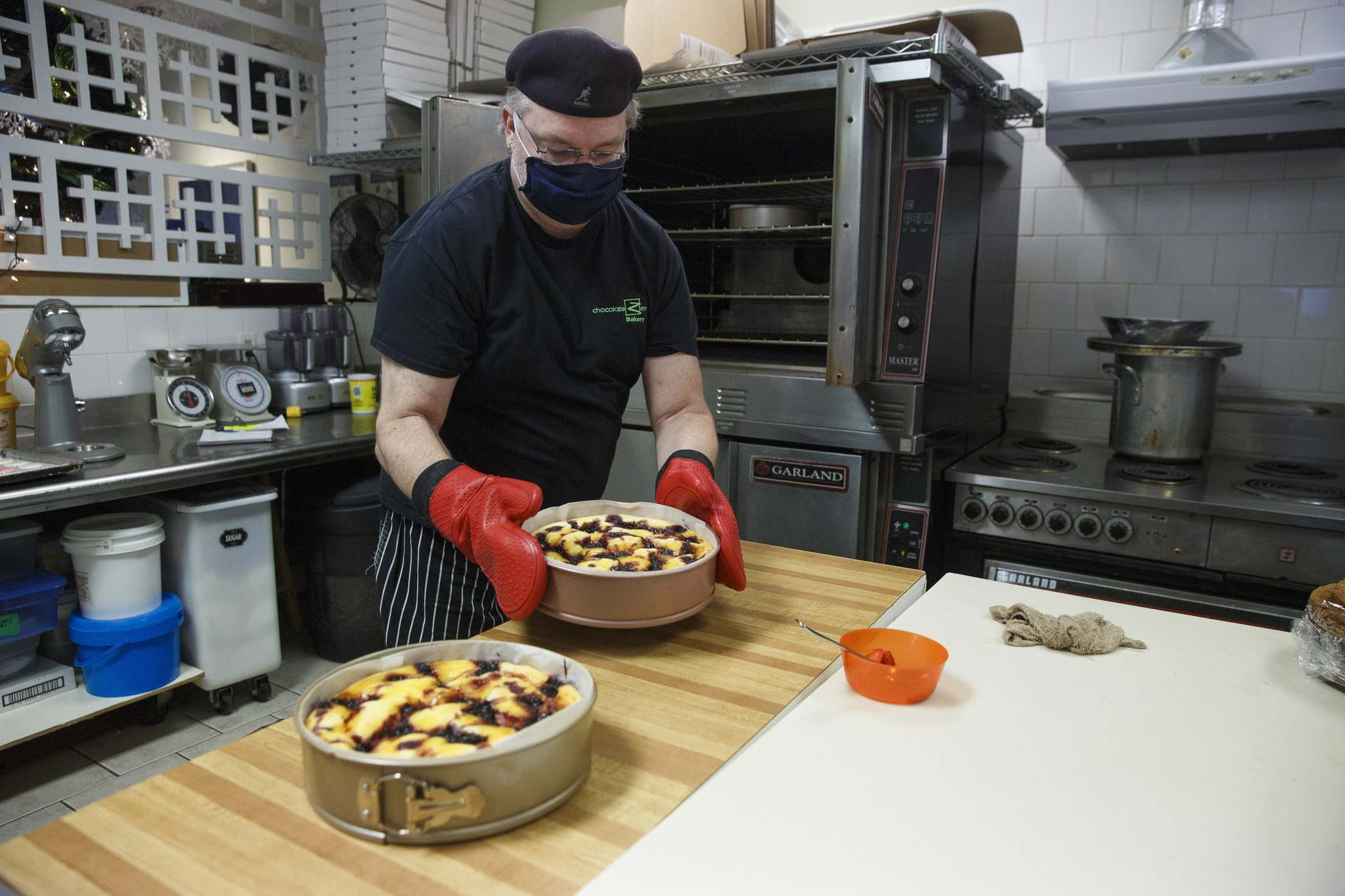 Doug Krahn takes cheesecakes out of the oven. (Mike Deal / Winnipeg Free Press)</p>