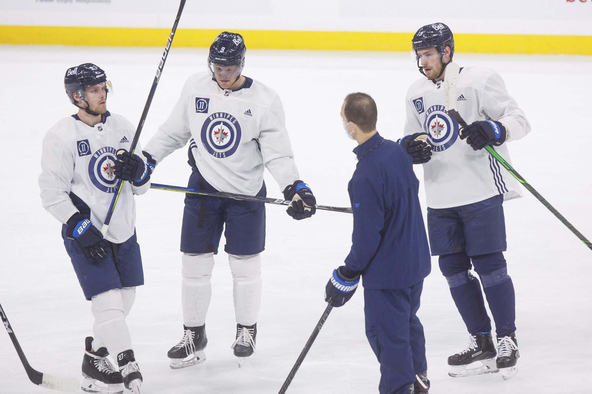 Nikolaj Ehlers, Andrew Copp, and Pierre-Luc Dubois talk with associate coach Jamie Kompon during practice Monday morning.