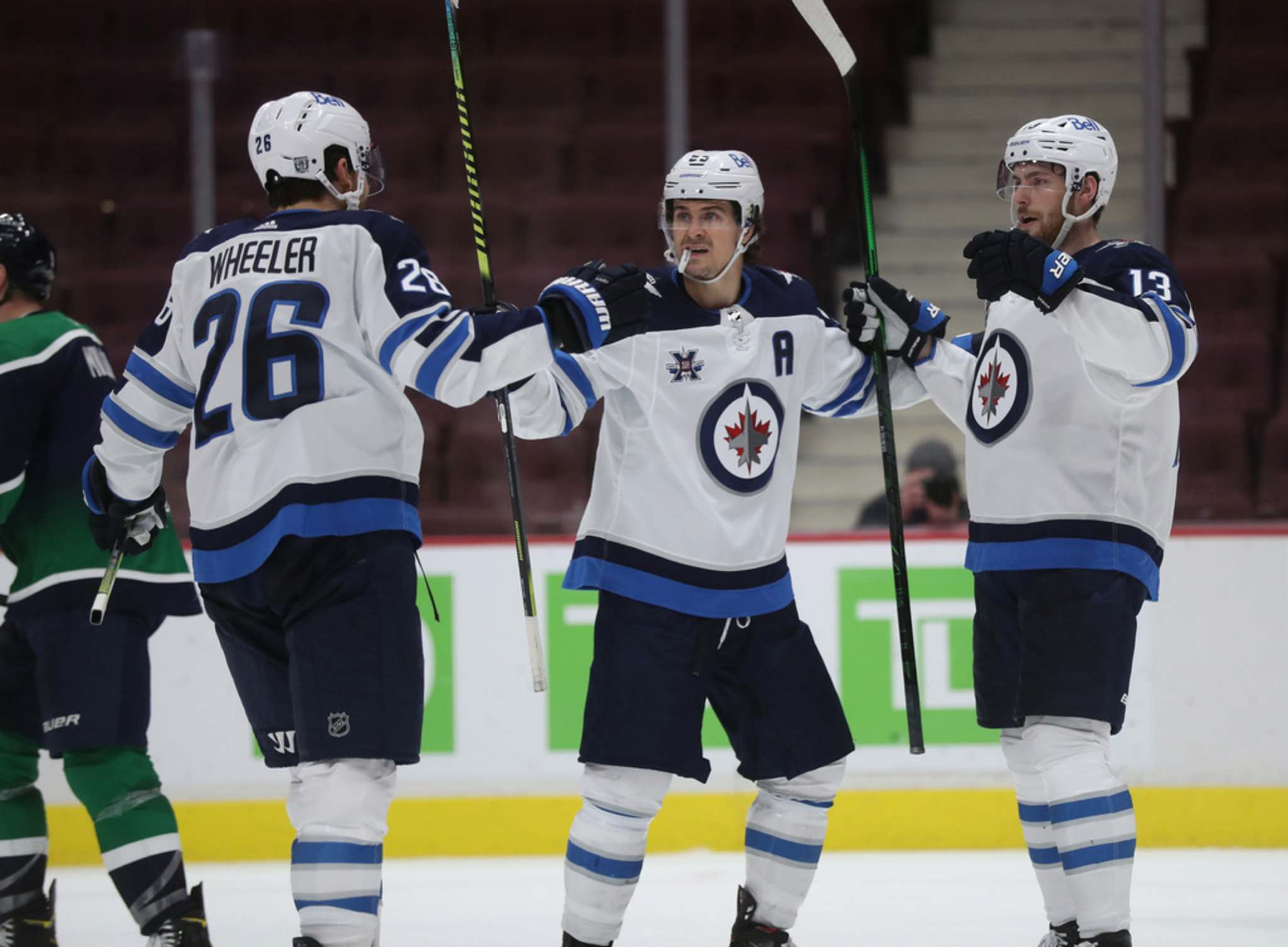 Blake Wheeler and Mark Scheifele celebrate with Pierre Luc Dubois after Dubois scored his first goal with the Winnipeg Jets during the second period against the Vancouver Canucks in Vancouver, Sunday. (TREVOR HAGAN / WINNIPEG FREE PRESS)</p>