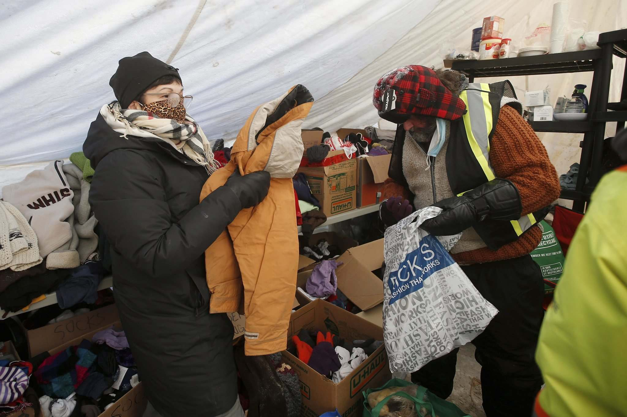 Volunteers Eva Wilson-Fontaine, left, and Tony DeRose sort donations at the clothing drop-off.