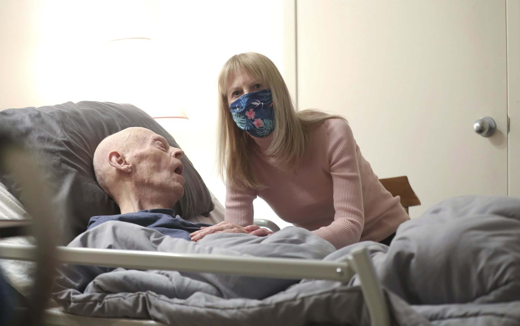 Linda-Beth Marr sits next to her dad, 95-year-old dad William Marr, as he sleeps in his bed which is part of a shared living space with Linda and her husband.