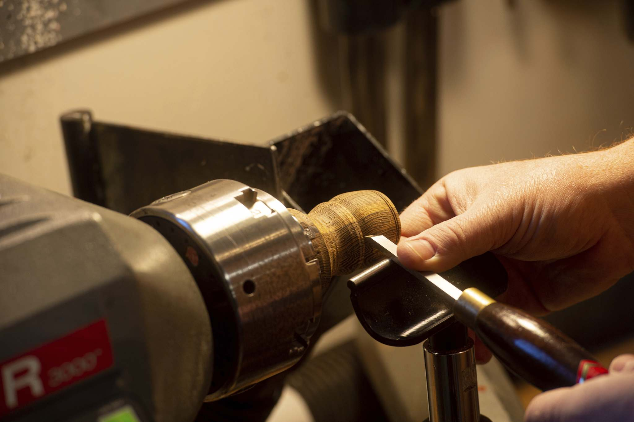 Kydd crafts a wooden shaving brush on his lathe inside his home workshop.