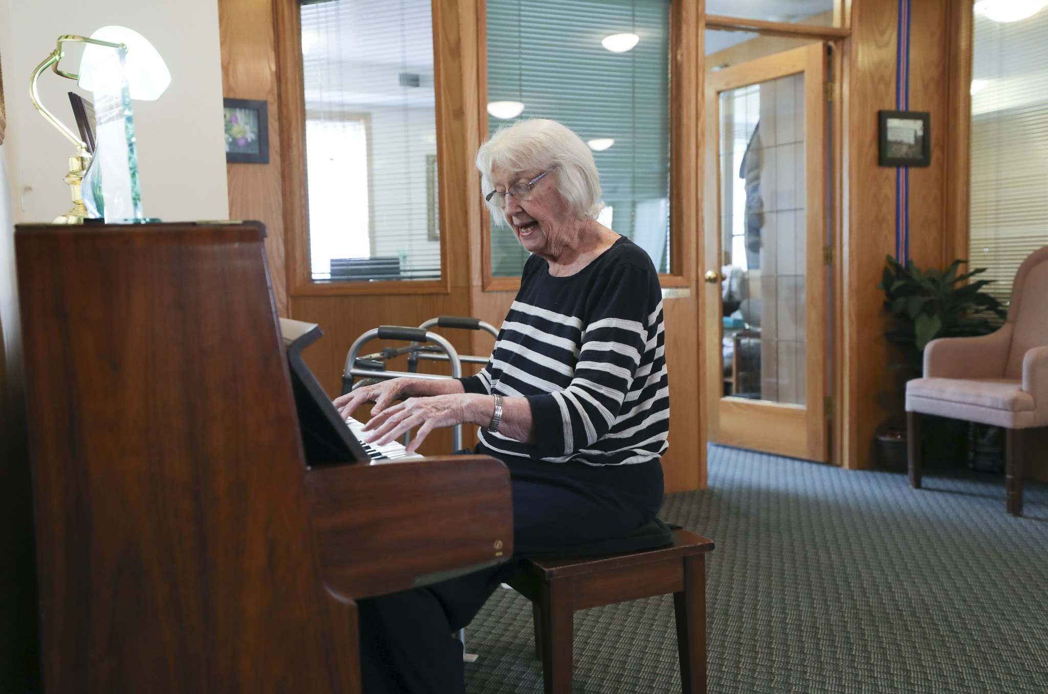Joan Guttormisson plays the piano for guests at centre.