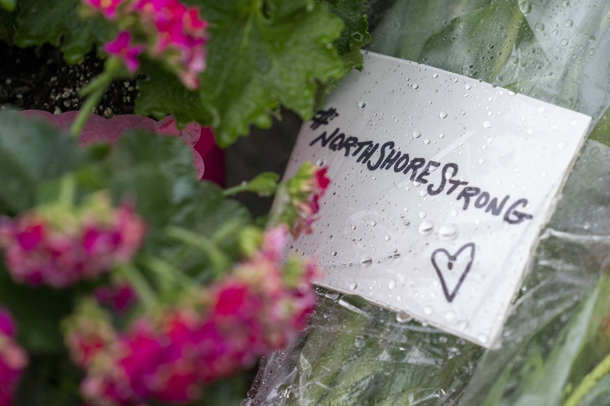 Flowers and notes are seen at a makeshift memorial for the stabbing victims that were attacked by Yannick Bandaogo on Saturday.